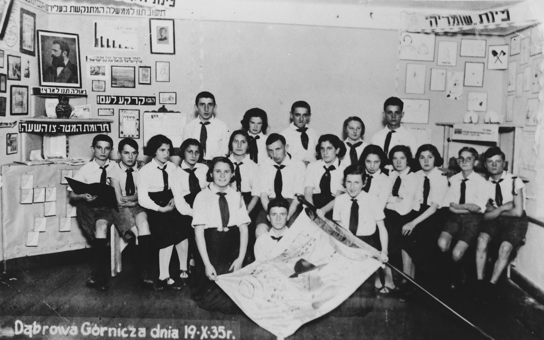 A large group of children from a Zionist youth movement in Dabrowa Gornicza poses in a room decorated with posters and a photograph of Theodore Herzl.
