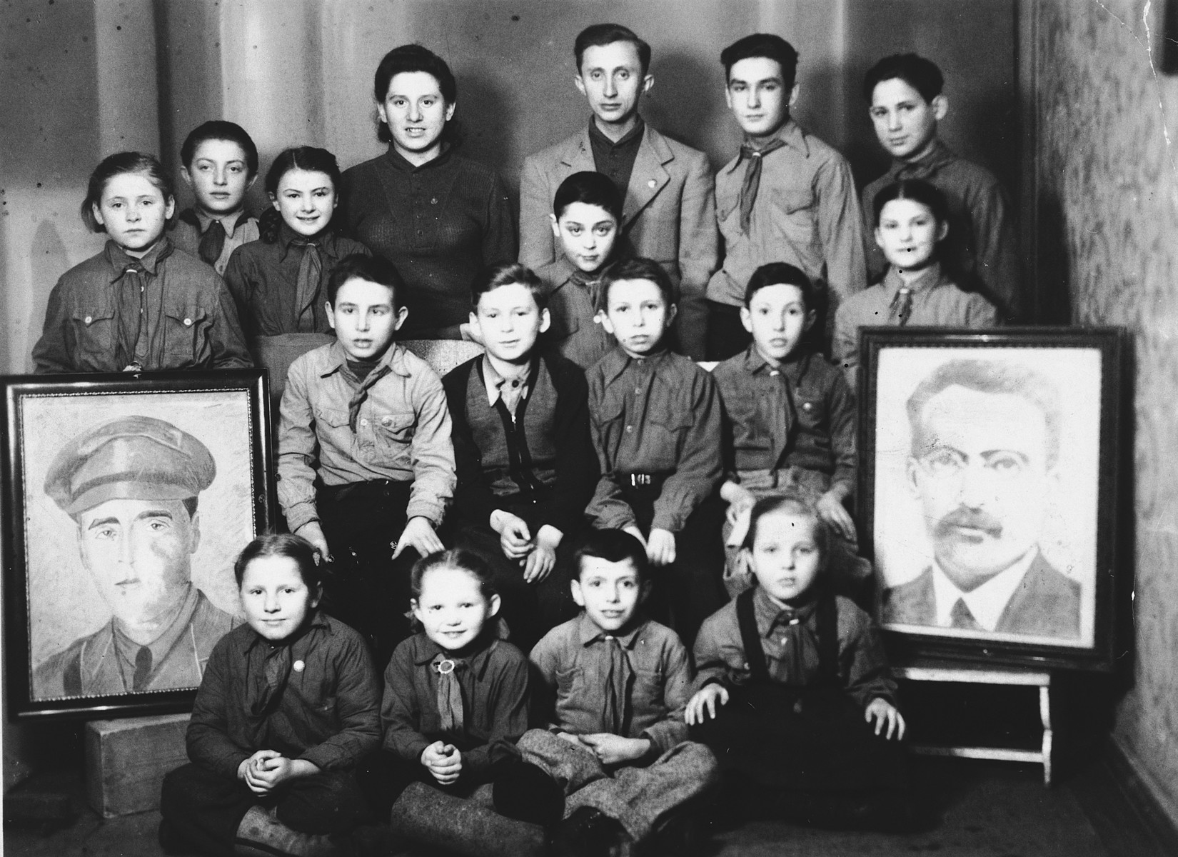 Children belonging to the Zionist  youth movement Dror in Poland pose between portraits of two Zionist heroes, Joseph Trumpeldor and Ber Borochov.  Among those seated on the floor is Leah Szain.