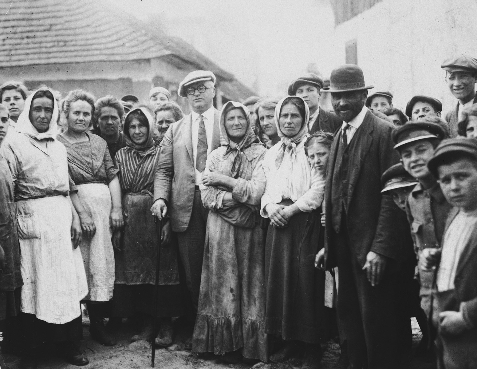 Group portrait of Jewish friends and relatives standing in the town square of Drohobycz, taken on the occasion of a visit by Harry Handel (former resident of Drohobycz) from America.  Handel is pictured standing in the center left, holding a walking stick.