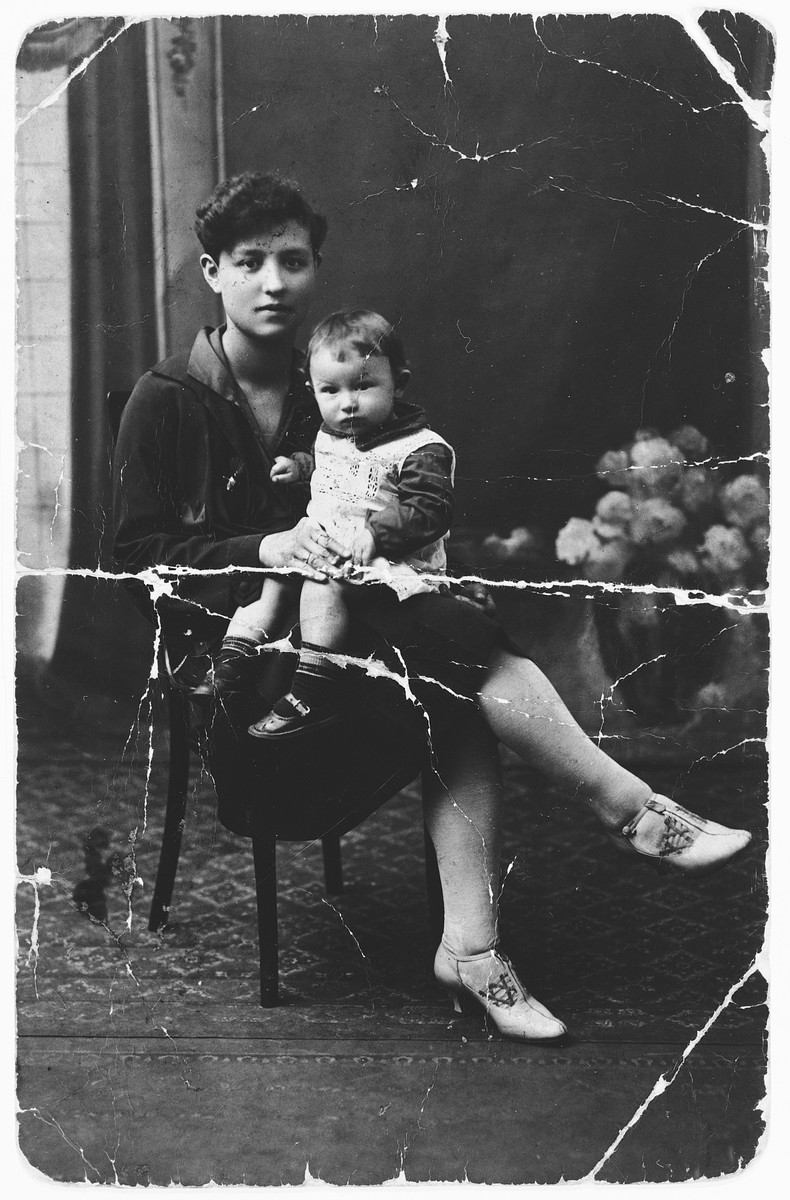 A Jewish mother holds her baby on her lap.  Pictured are Chaya Perla Frydland and her oldest daughter, Taube.