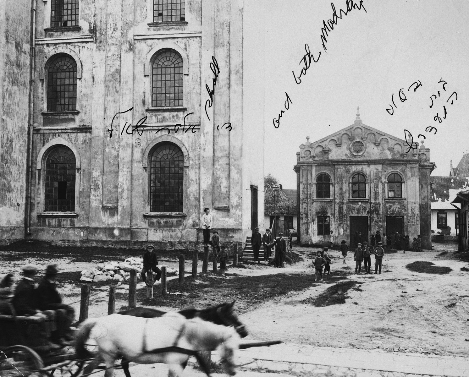 Passengers in a horse-drawn carriage ride through the public square of Drohobycz, past the large synagogue.  On the left is the large synagogue.  On the right is the smaller house of prayer, (Bet Midrash).