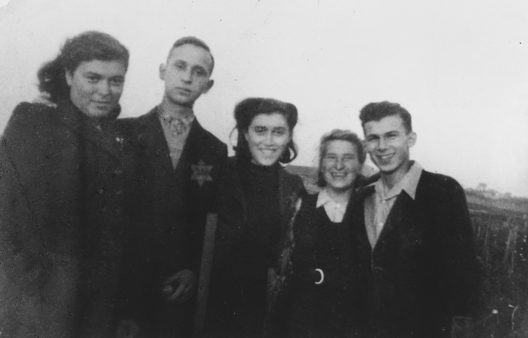 Group portrait of five young people in the Dabrowa ghetto wearing Jewish stars.  Those pictured include Moniek Gorset, Mania Kornfeld, Zosia Spokojna and Este Zelten.