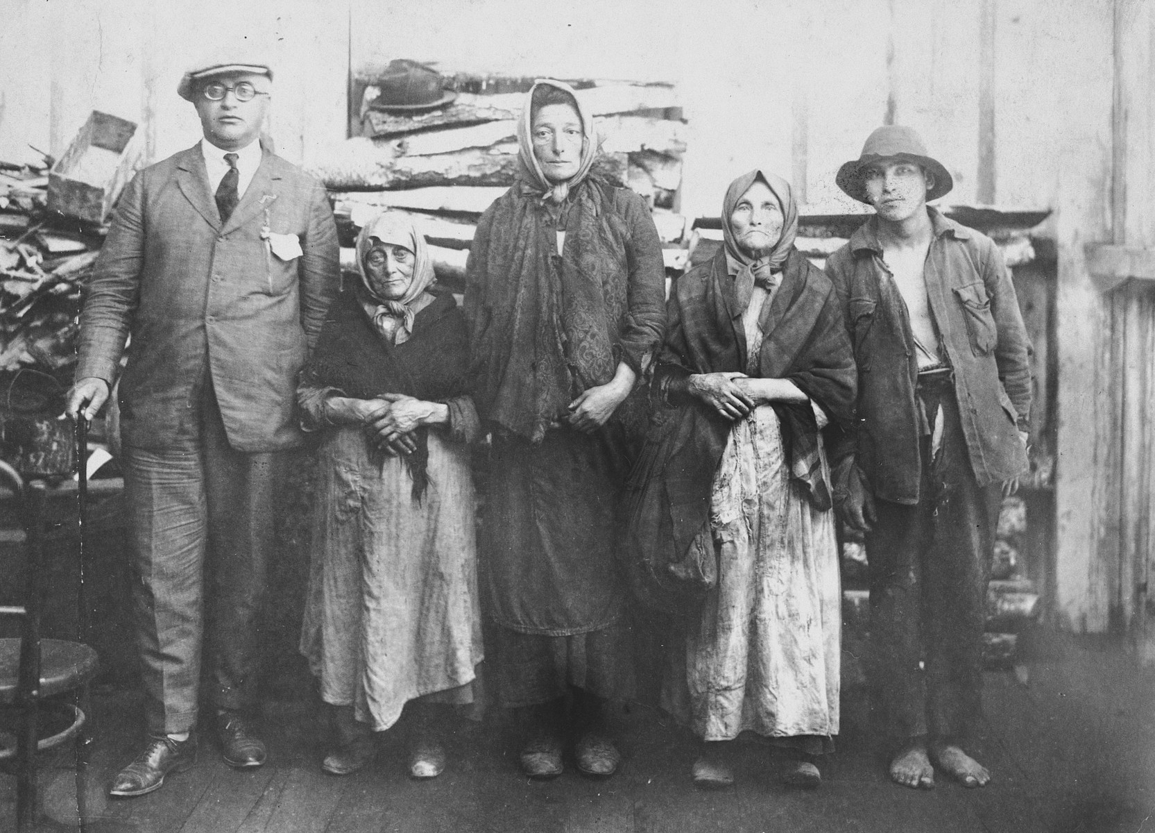 A group portrait of impoverished Jews in Drohobycz standing in front of a stack of lumber.  On the far left is Harry Handel, who is visiting from America.