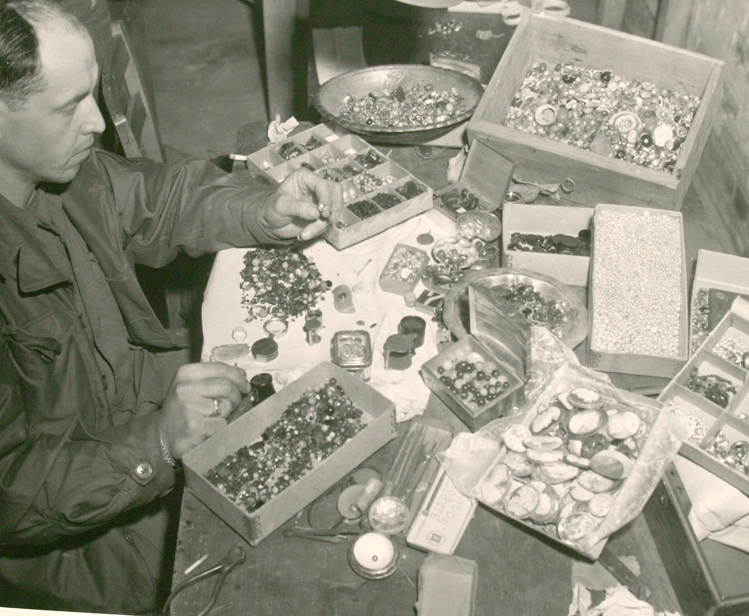 "An American soldier views an array of stones and other valuables confiscated from prisoners in the Buchenwald concentration camp and recovered by U.S. troops after the liberation of the camp.  Original caption reads: ""German loot from Buchenwald atrocity victims.  These stones are a few of the thousands of valuables the Germans removed from their victims in the Buchenwald Concentration Camp near Weimar, Germany.  The loot was discovered by the First U.S. Army troops in a cave adjoining the camp."""