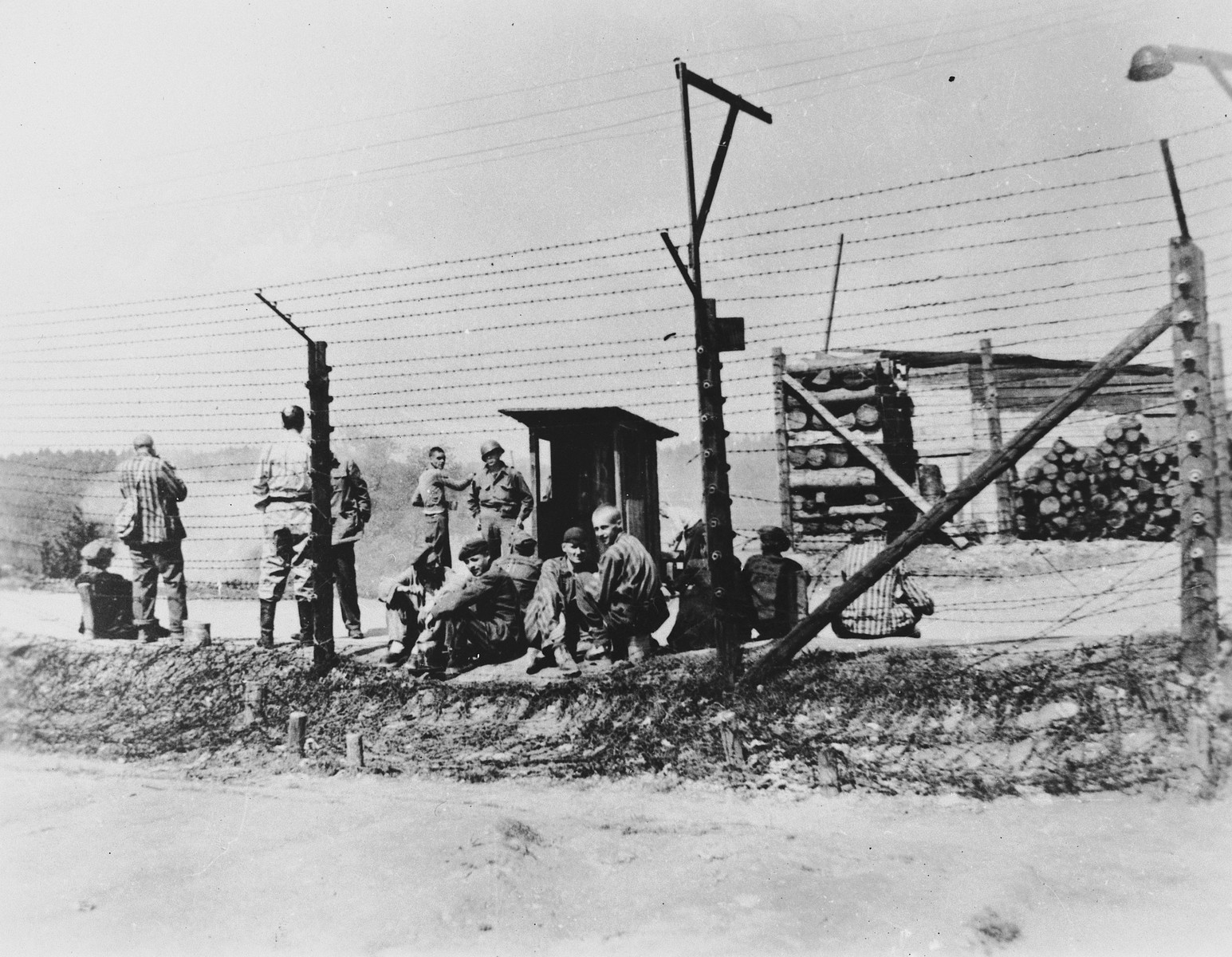 Liberated prisoners gather by the barbed wire fence in front of stacked wood in an unidentified concentration camp.