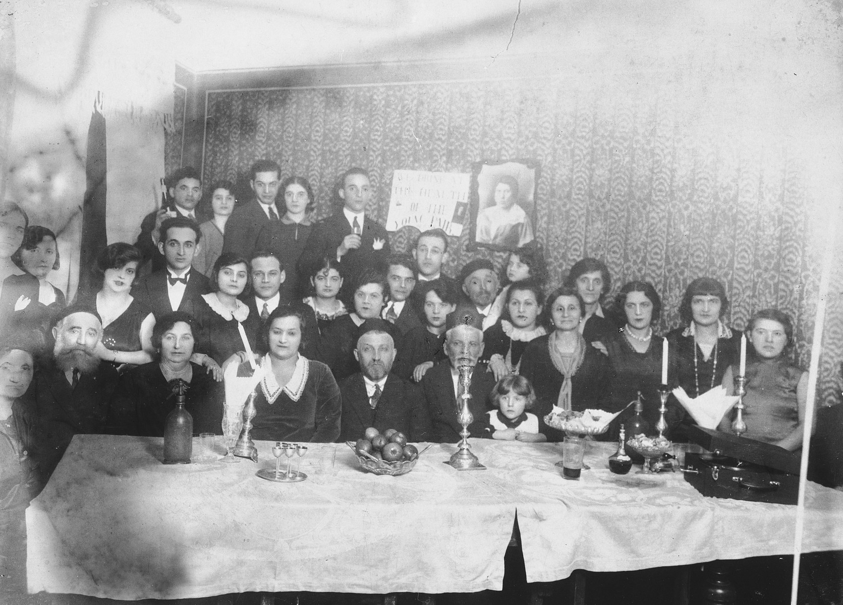 "The Safirsztajn family gathers to celebrate the marriage of Mordechai Safirsztajn who had immigrated to the United States.  The sign hanging on wall behind them reads: ""We drink to the health of the young couple.""  Among those pictured is Regina Safirsztajn (far right), one of the four women who was hanged for her participation in the Auschwitz uprising.   Pictured are last row, left to right: Ajzyk Safisrsztajn, unknown, [first name unknown] Gold, unknown, and [first name unknown] Gold.  Middle row: unknown, [first name unknown] Safirsztajn, wife of Wolf Safirsztajn, Wolf Safirsztajn, [first name unknown] Najmark, [first name unknown] Najmark, [first name unknown] Najmark, Chana Safirsztajn Ickowicz, Adek Eizel Safirsztajn, Abel Ickowicz, Szaja Ickowicz, Bronia Ickowicz, Tonia Safirsztajn, [first name unknown] Safirsztajn, ""Mima"", [first name unknown] Gold, [first name unknown] Gold, and Regina Safirsztajn.  Seated in first row, left to right: unknown, Icie Safirsztajn, Golda Safirsztajn, Karola Safirsztajn Najmark, Jakub Najmark, Josef Najmark Rozia Ickowicz."