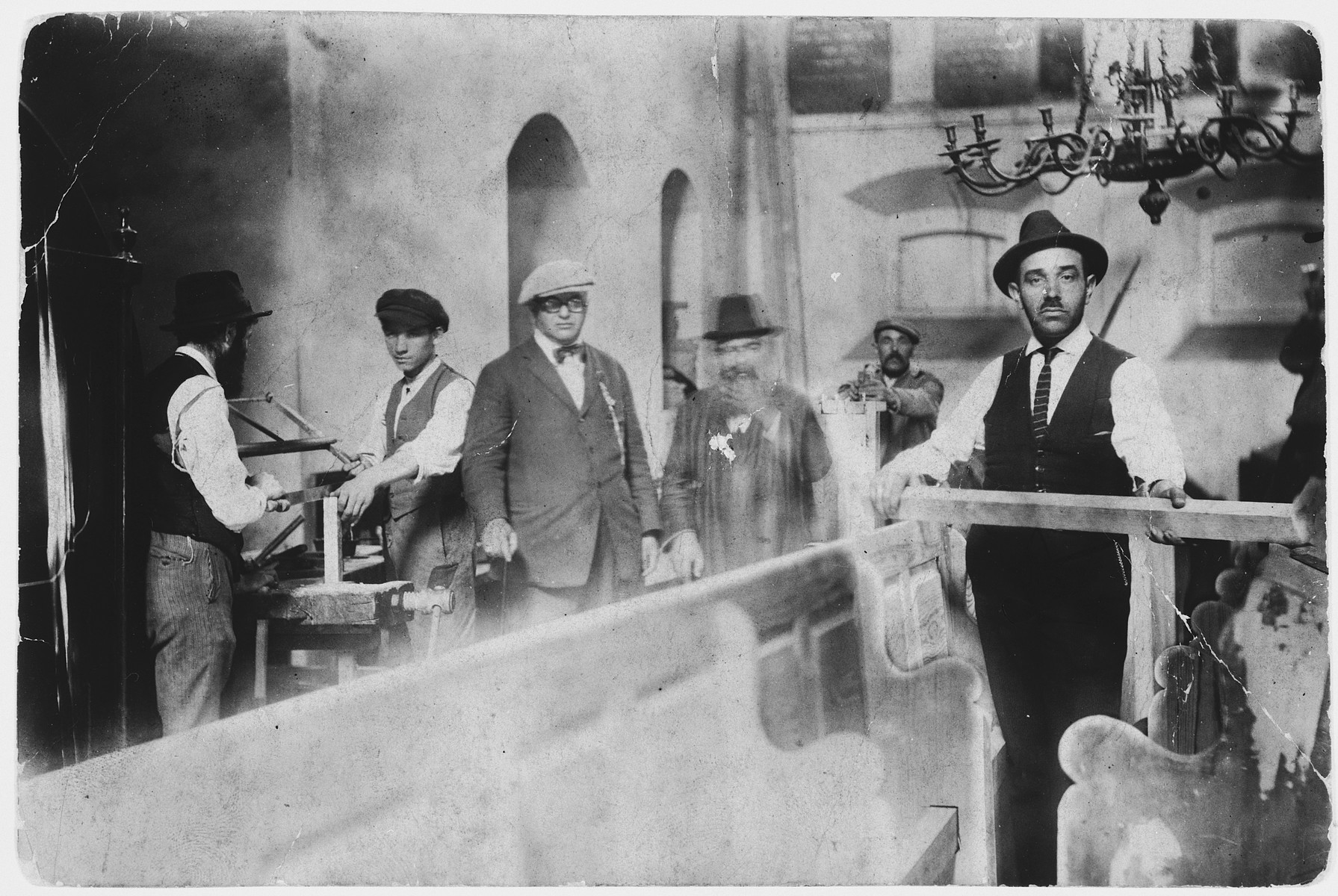 Harry Handel, a Jewish-American visitor (formerly from Drohobycz) surveys carpenters working inside a synagogue.