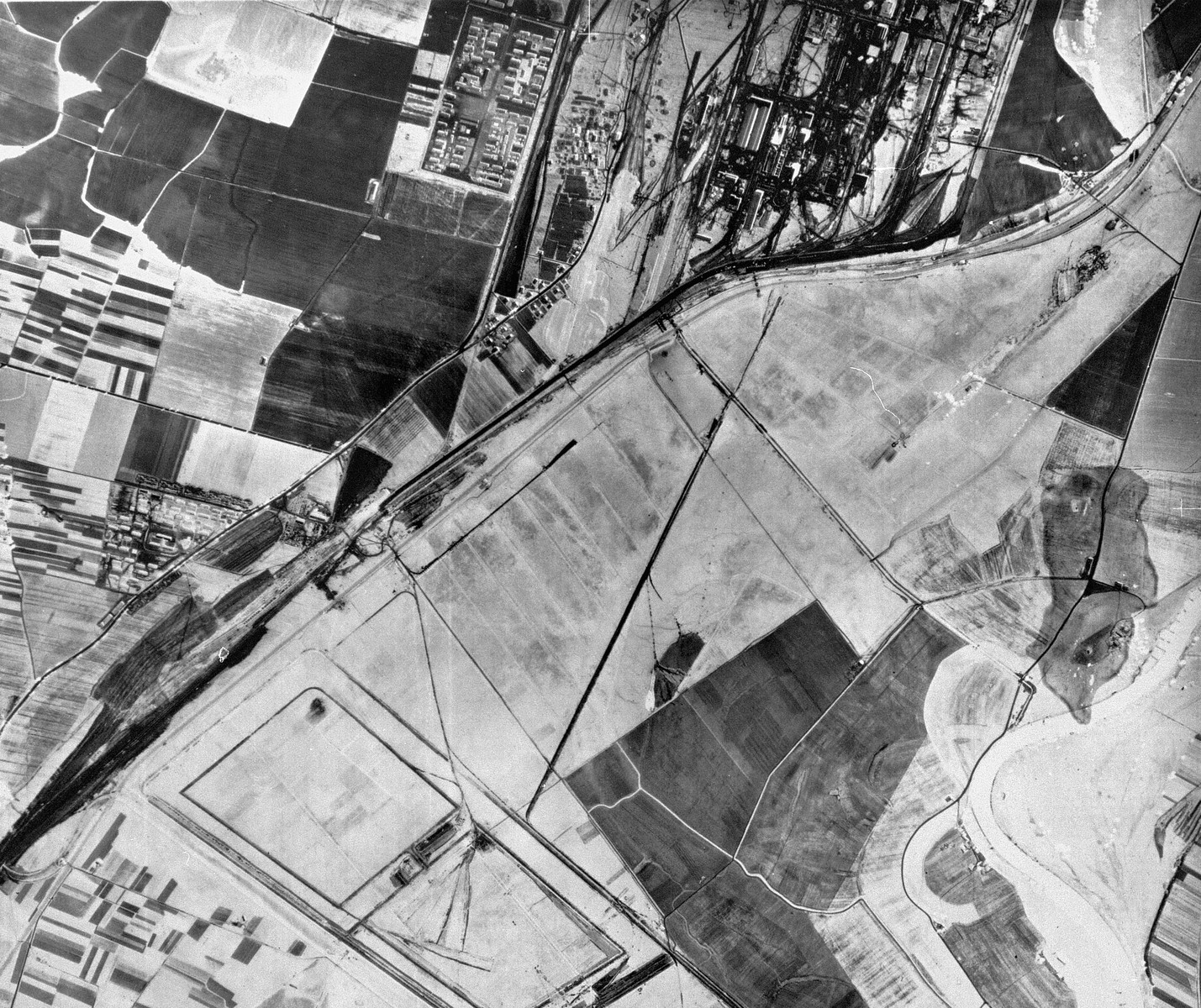 "An aerial reconnaissance photograph of the Auschwitz area showing a partial view of the I.G. Farben ""Buna"" complex with the adjacent Monowitz (Auschwitz III)."