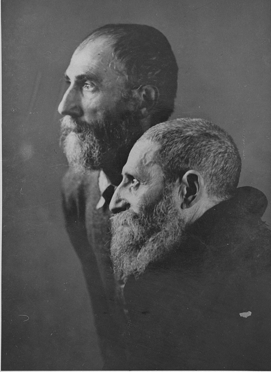 "Portrait of two Jewish men from Subcarpathian Rus taken upon their arrival in Auschwitz-Birkenau.   These two religious men were taken to the camp photographic laboratory in Block 26 to have their picture taken in order to document a certain ""racial type"".  They were later sent to the gas chambers, but not before they were humiliated by having to uncover their heads."