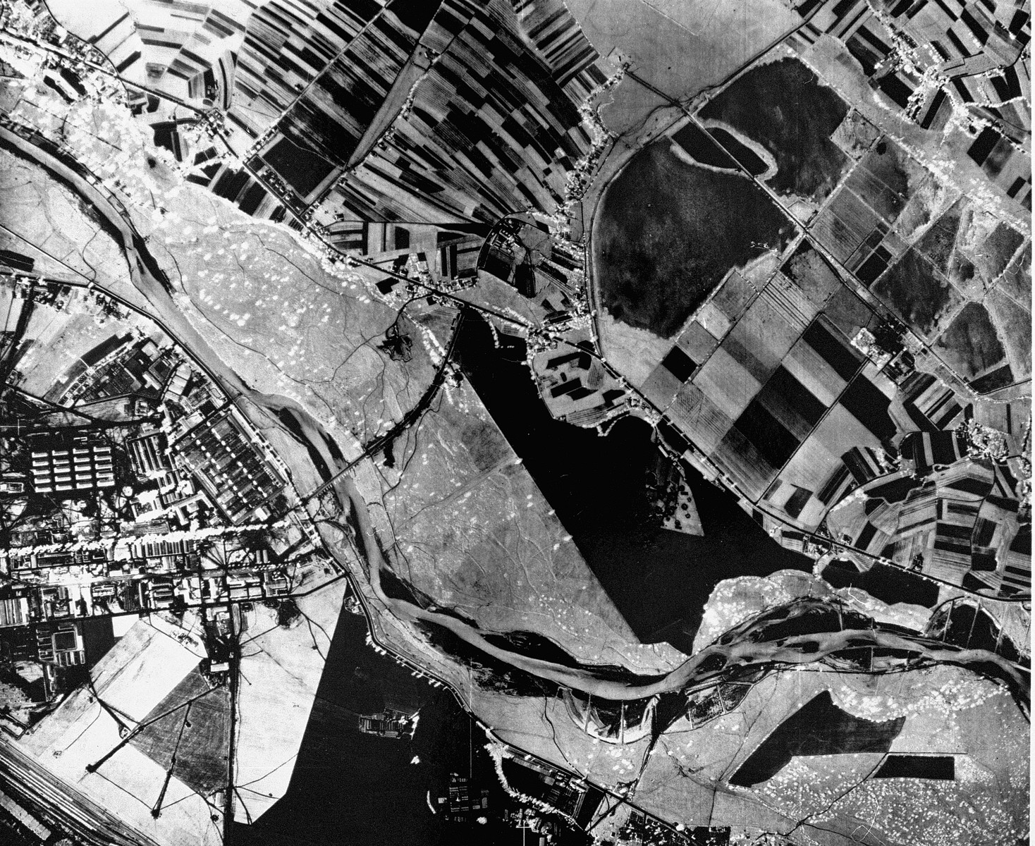 An aerial reconnaissance photograph of  Auschwitz I showing the administrative and living areas as well as the railway staging area in the upper corner.