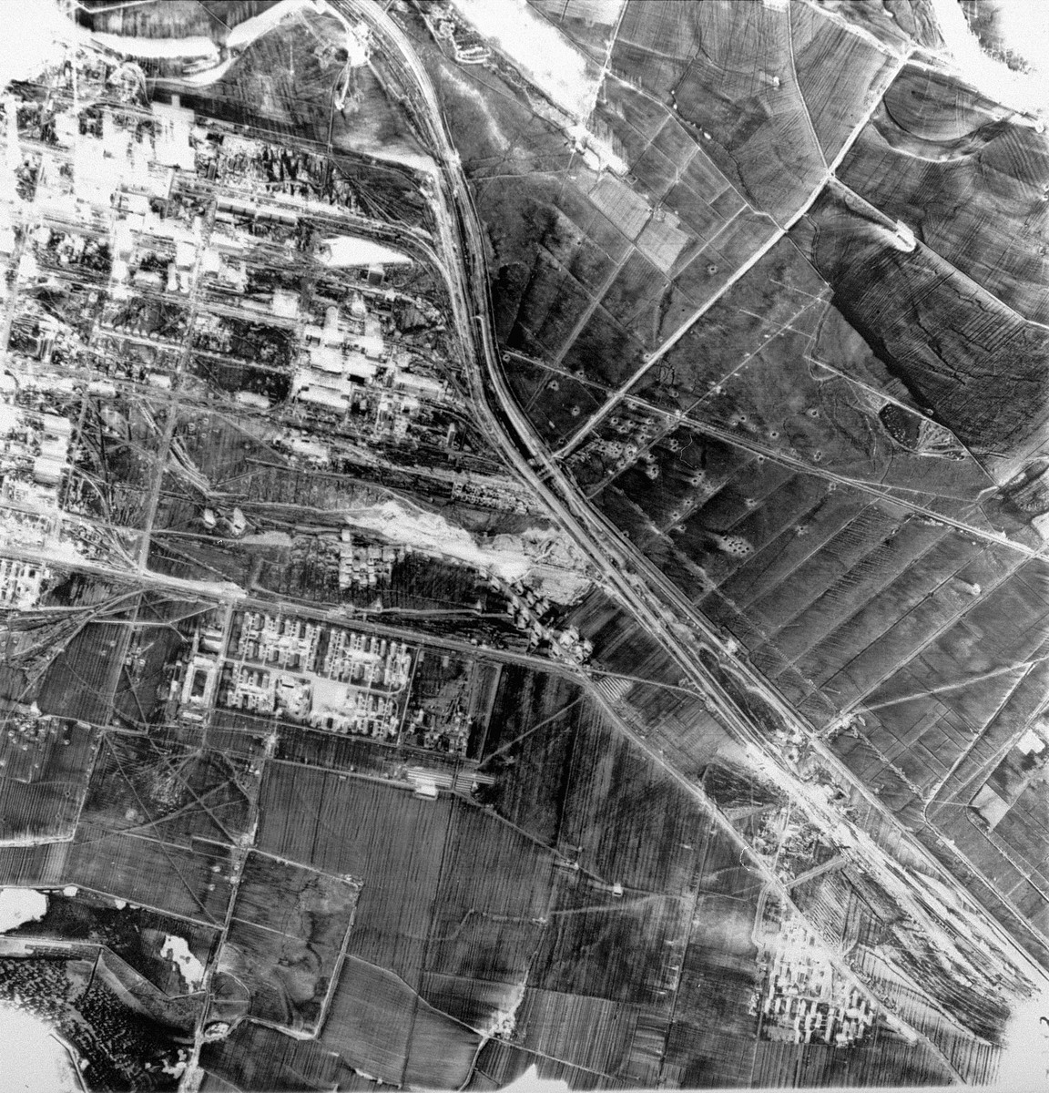 An aerial reconnaissance photograph showing the I.G. Farben complex.  [oversized photo]   Pictured here: IG Farben plant (top), Auschwitz III Buna (Monowitz) camp (left) and slave labor camp fno 5 (right).
