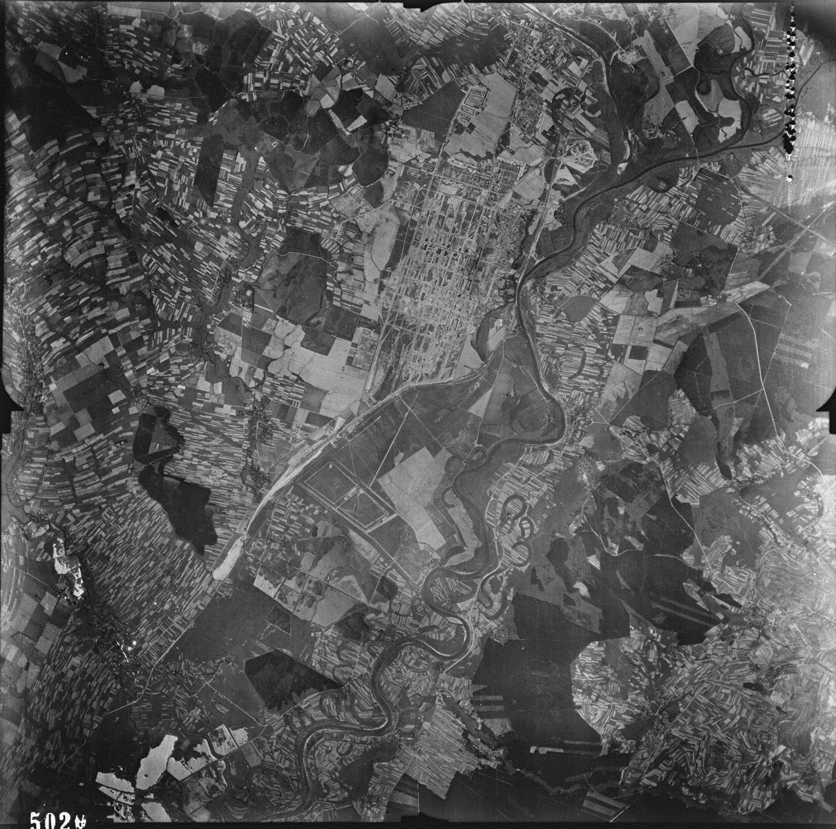 "An aerial reconnaissance photograph showing Auschwitz III (Monowitz) and the IG Farben ""Buna"" plant. [oversized photograph]  Mission:  60 PRS/462 60 SQ;  Scale: 1/54,000;  Focal Length: 6"";  Altitude: 27,000'"