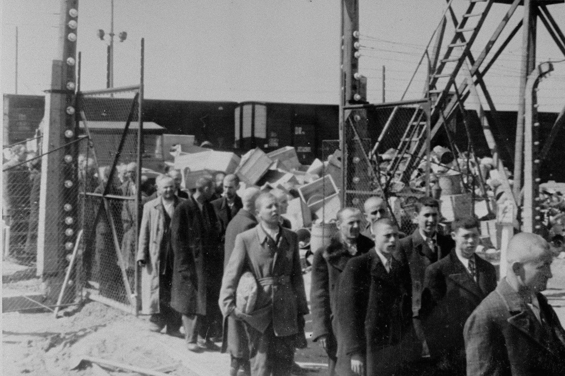 Jews from Subcarpathian Rus who have been selected for forced labor at Auschwitz-Birkenau, are marched to another section of the camp.  Behind them are huge piles of personal property confiscated from the deportees.