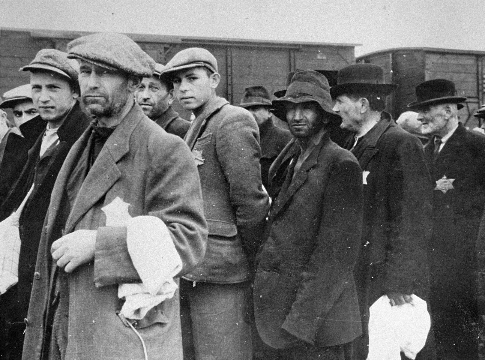 Jewish men from Subcarpathian Rus await selection on the ramp at Auschwitz-Birkenau.  Among those pictured are the brothers Martin and Simon Herskovics (behind and at the far left), and their father, Moshe, in the left foreground.  Behind the Herskovics' is Yechiel Slomovics and his son Motti; and in the center, wearing a peasant hat is Jossel Schmajovics.  Also, pictured is Solomon Hershkovitz and Zaliman Hershovitz.