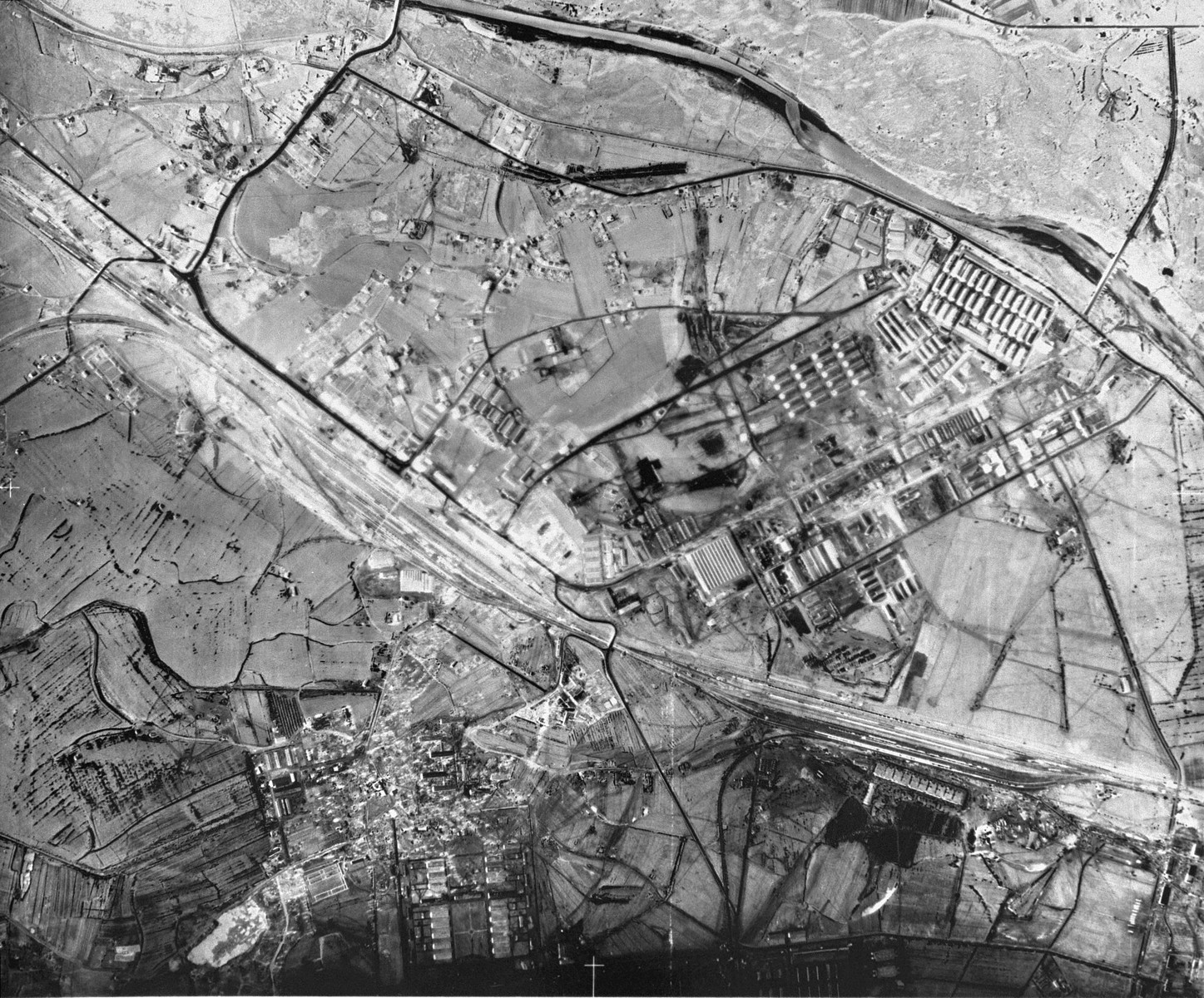 An aerial reconnaissance photograph of Auschwitz I showing the prisoners' barracks and administrative buildings which are visible along with the main railway lines.