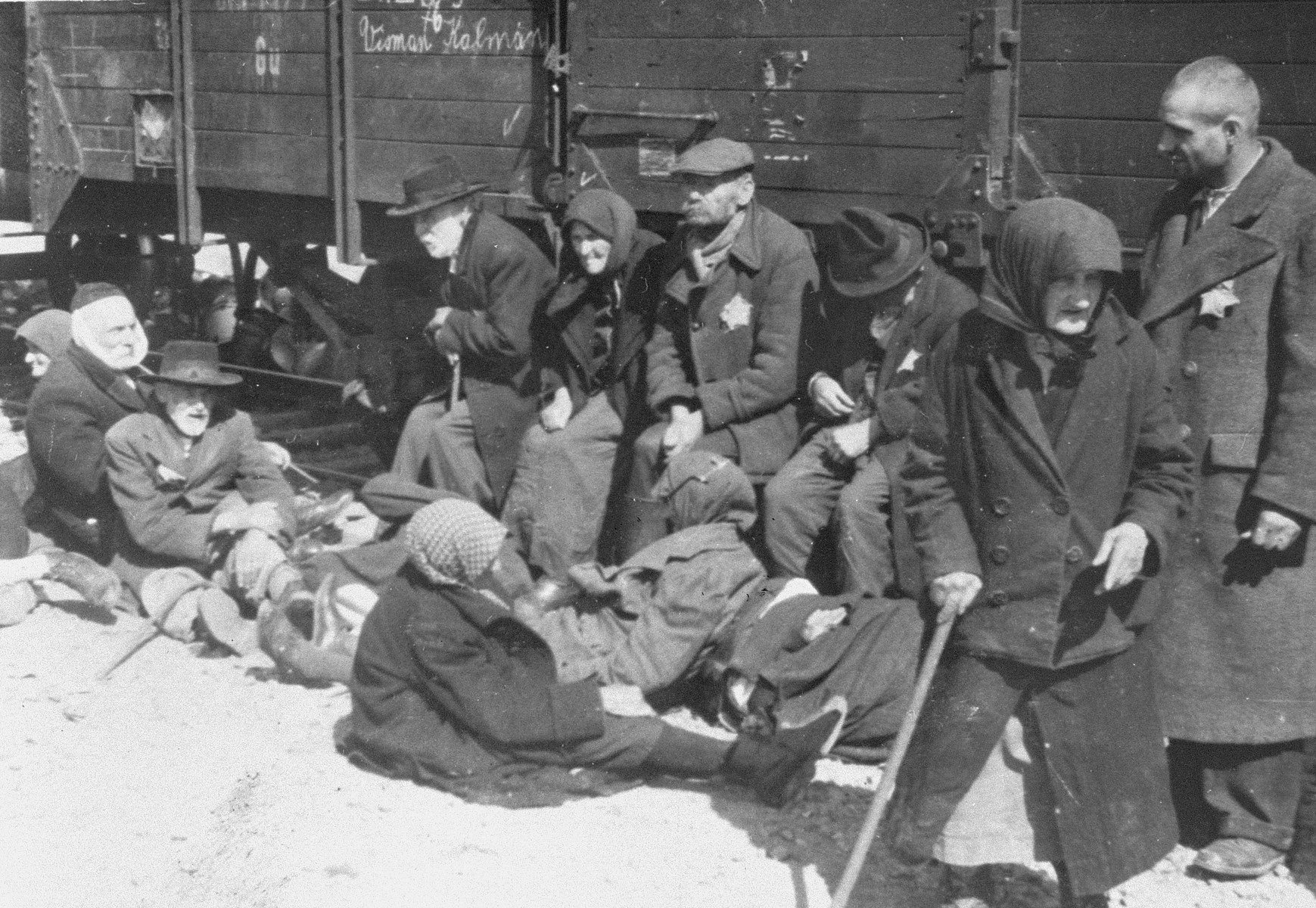 A group of elderly Jews from Subcarpathian Rus sit alongside the train on the ramp at Auschwitz-Birkenau. In time these people will be put on trucks and driven to the gas chamber.   Sitting next to the train on the left are Lili Jacob's maternal grandparents, Abraham and Sheindele Jacob.  Seated on the ground at the far left is Henryk Naftoli Herz Adler.  He is wearing a handkerchief to cover his face because his beard was forcibly cut off.  Seated in front of him is Samuel (Sandor) Ben Yehuda Kohn.