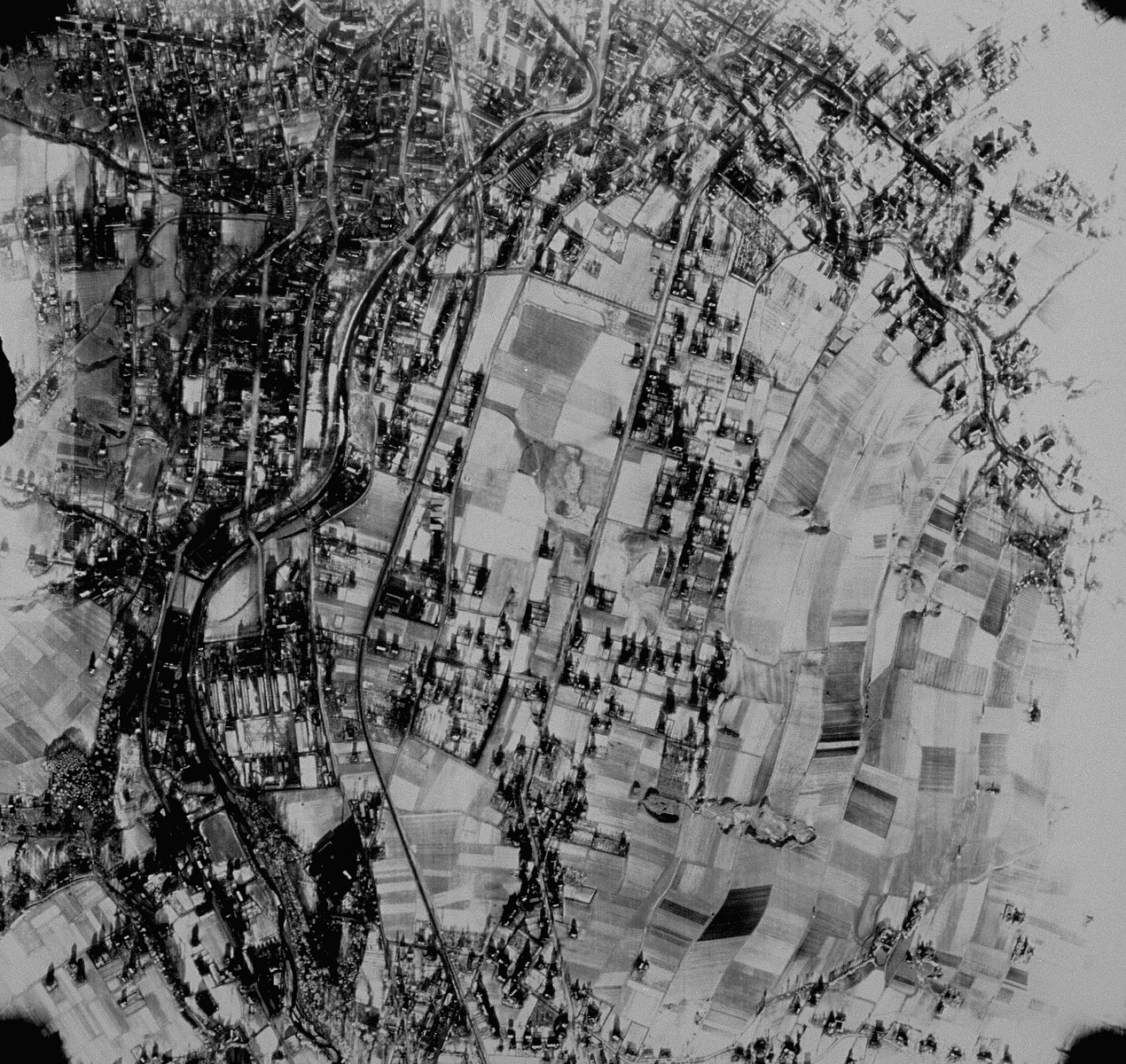 "An aerial reconnaissance photograph of the Auschwitz concentration camp showing Auschwitz I under heavy snow cover.  Mission:  5SG/1085 5PG;  Scale: 1/42,000;  Focal Length: 6"";  Altitude: 21,000;  [oversized photograph]"