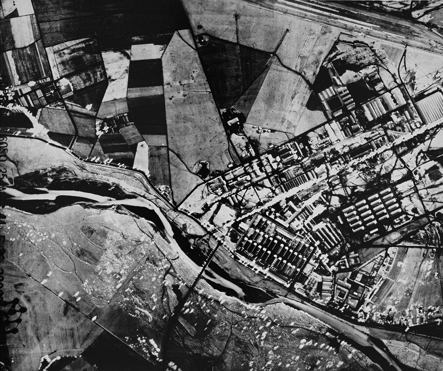 An aerial reconnaissance photograph of Auschwitz I showing the administrative area as well as a portion of the rail lines leading to the camp.