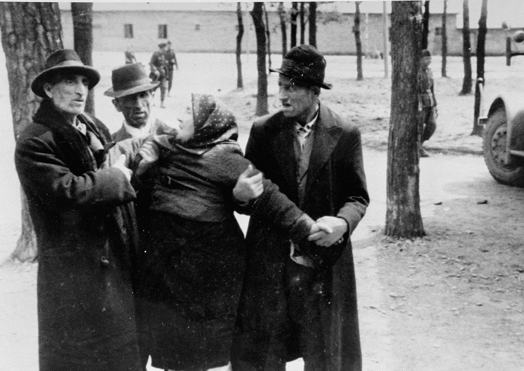 An elderly Jewish woman from Subcarpathian Rus is being held in place by three Jewish men [after having been separated from family members during the selection].