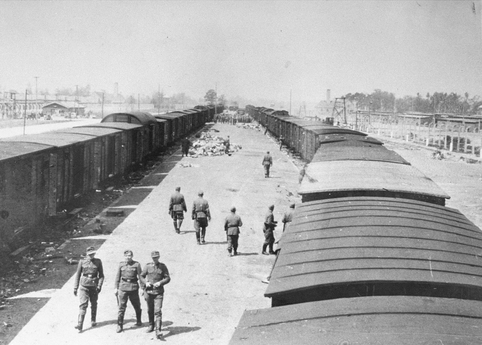 SS guards walk along the arrival ramp at Auschwitz-Birkenau.  The Birkenau arrival ramp was completed only weeks before this photo was taken.  Formerly the deportation trains arrived at a ramp that was half a mile away.  Crematoria II and III can be seen in the far background.