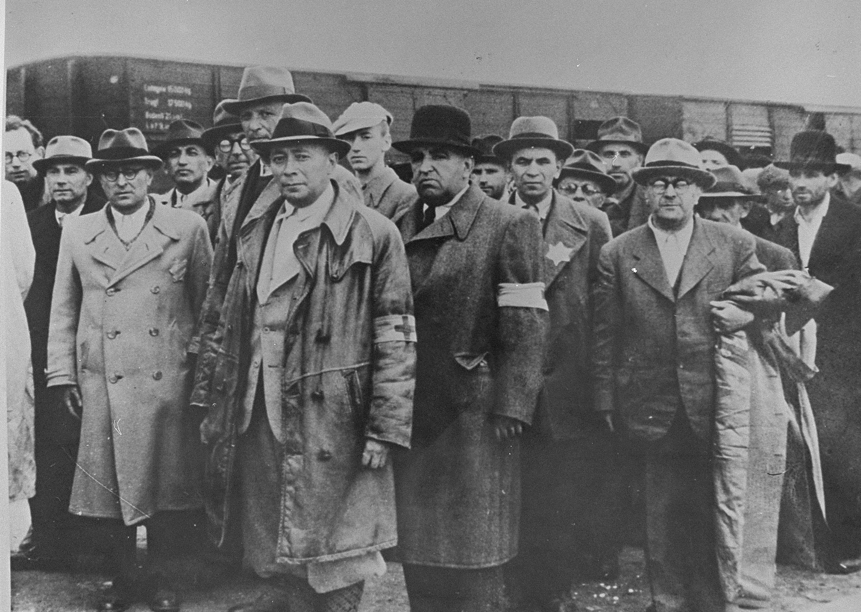 Jewish men from Subcarpathian Rus await selection on the ramp at Auschwitz-Birkenau.   Among those pictured are: Weishouse, a pharmacist, (second from the left); Dr. Kellerman (next to Weishouse); Adolf Abraham (wearing glasses behind Kellerman);. Gyury Kellerman (in a white hat); Istvan Balasza, a pharmacist (front row, right).  All are from the town of Tecso.  Also pictured is Ludwig Granat (center) wearing an armband and black hat.  The only known to have survived is Istvan Balasza.