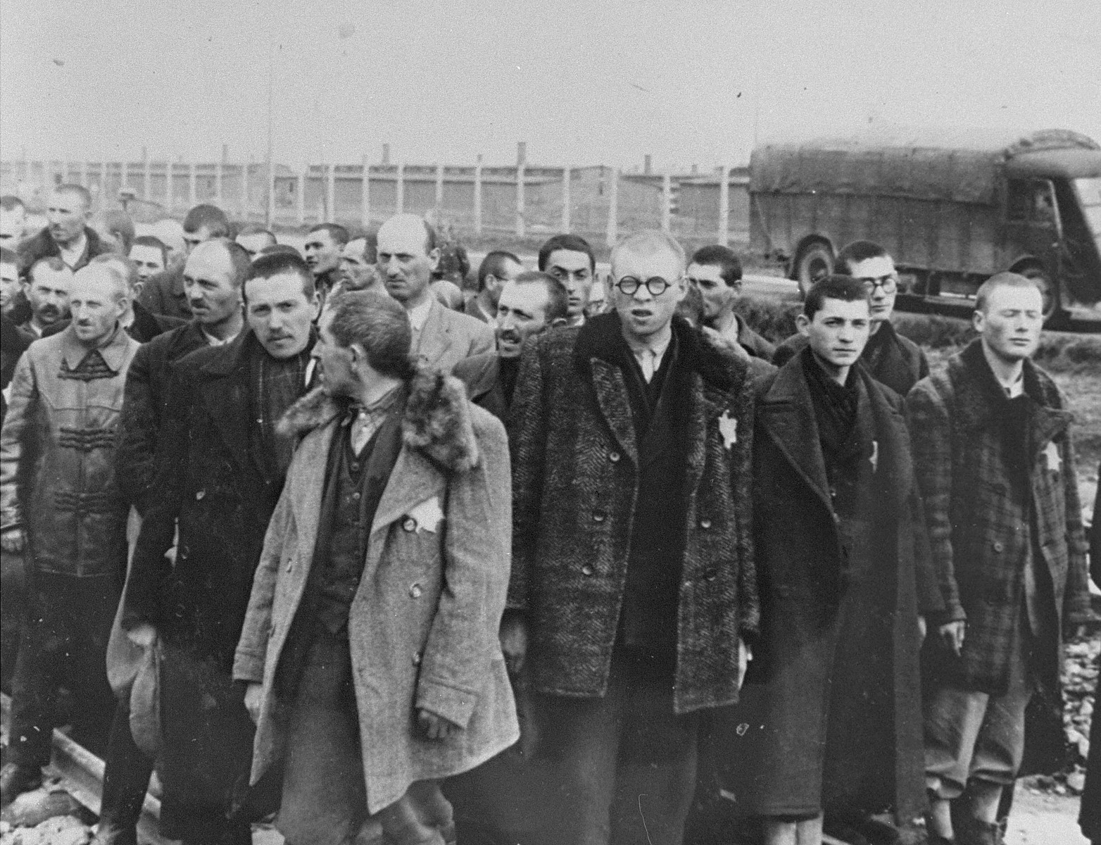 Jews from Subcarpathian Rus who have been selected for forced labor at Auschwitz-Birkenau, wait to be taken to another section of the camp.