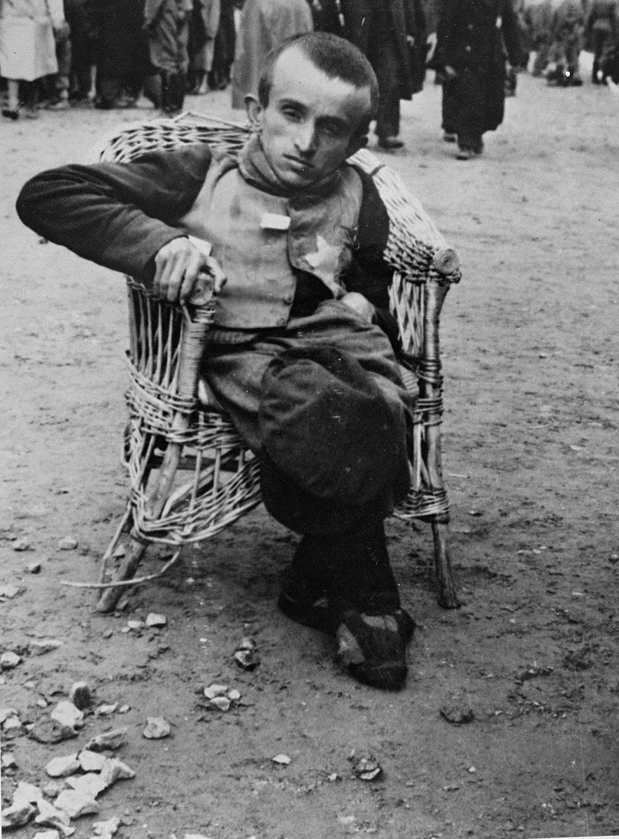 A Jewish dwarf who arrived on a transport from Subcarpathian Rus, is seated in a wicker chair on the ramp in Auschwitz-Birkenau.