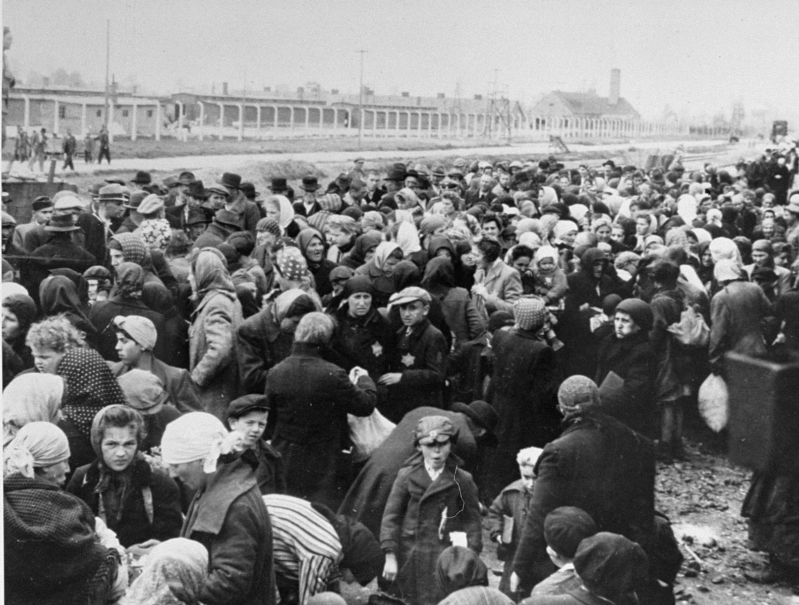 Jews from Subcarpathian Rus sit in a large group on one side of the ramp at Auschwitz-Birkenau before undergoing the selection process.   One of the crematoria is visible in the distance on the right.