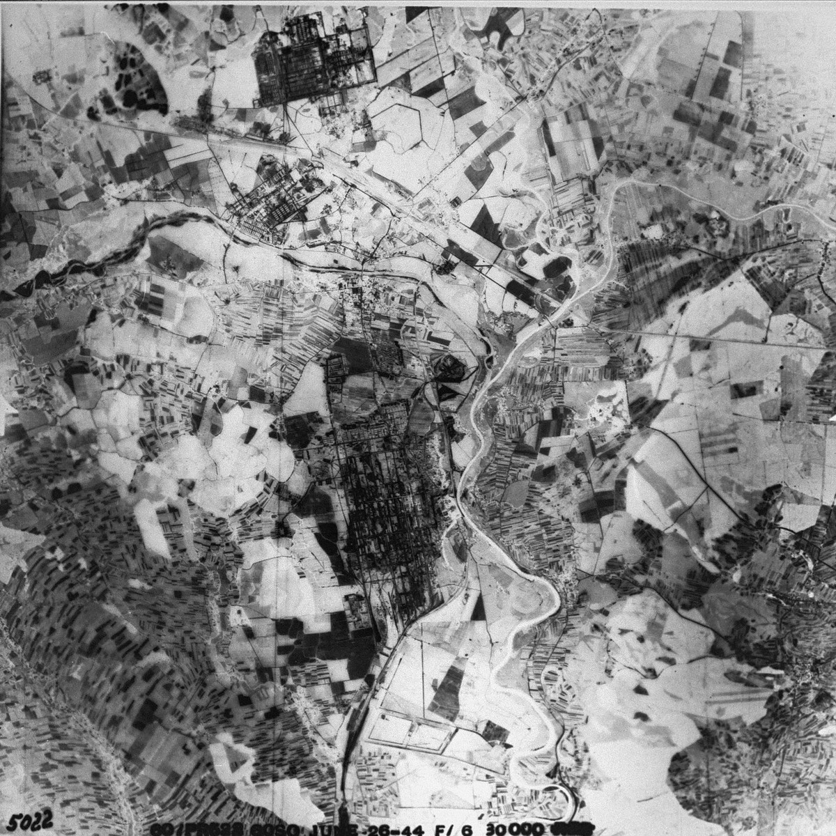 An reconnaissance aerial photograph of Auschwitz including Birkenau and Auschwitz III (Monowitz) next to the I.G. Farben synthetic oil and rubber manufacturing plant. [oversized photograph]