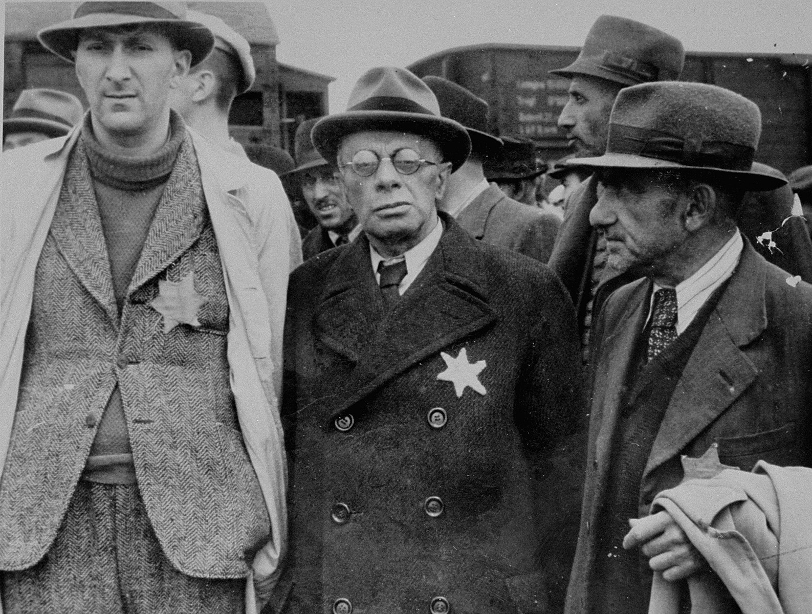 Three Jewish men from Subcarpathian Rus await selection on the ramp at Auschwitz-Birkenau.   Among those pictured are Dr. Henry Hegedush, a lawyer from Tesco (center), Dr. Lazar, a lawyer from Tesco (on the right) and Zoltan Kolos, a hotel owner from Tesco (behind Dr. Hegedush, on the left).