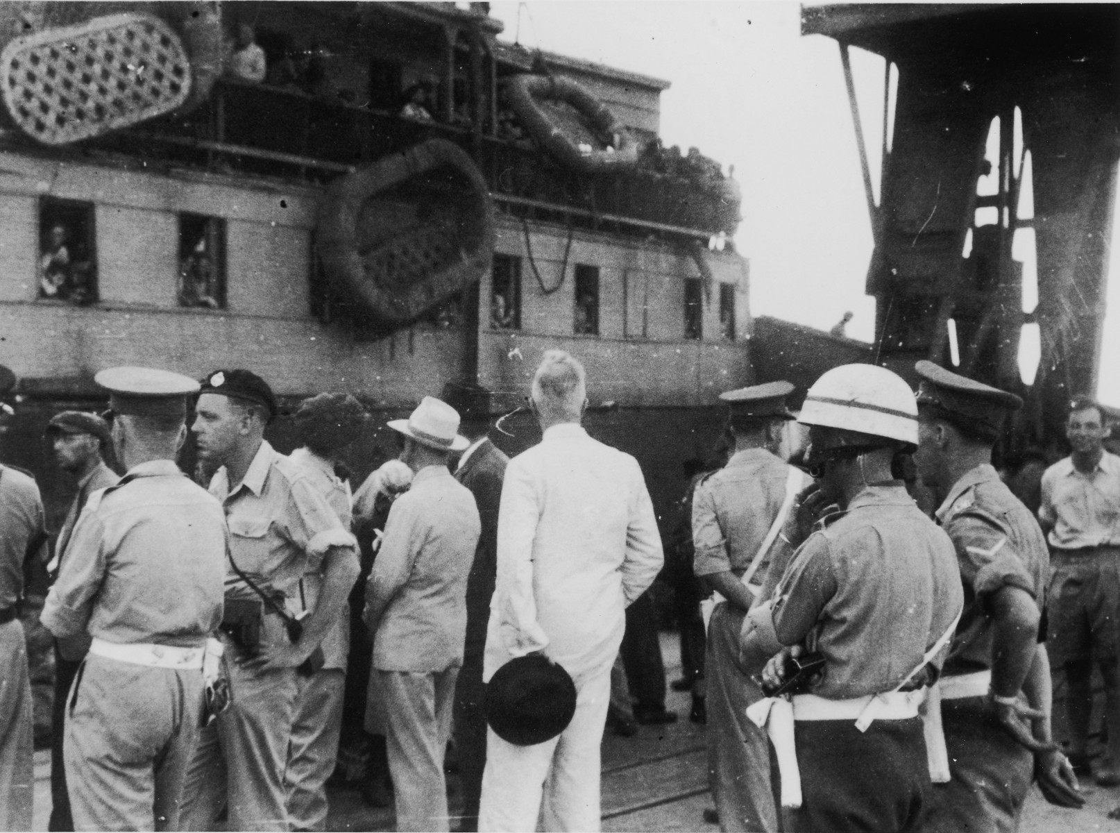 British soldiers on the pier in Haifa harbor oversee the offloading of passengers from the illegal immigrant ship, Exodus 1947, while a United Nations official (in the white suit) observes the process.