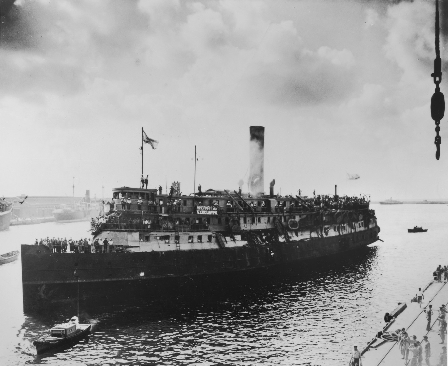 The battered illegal immigrant ship, Exodus 1947, is towed into Haifa harbor.