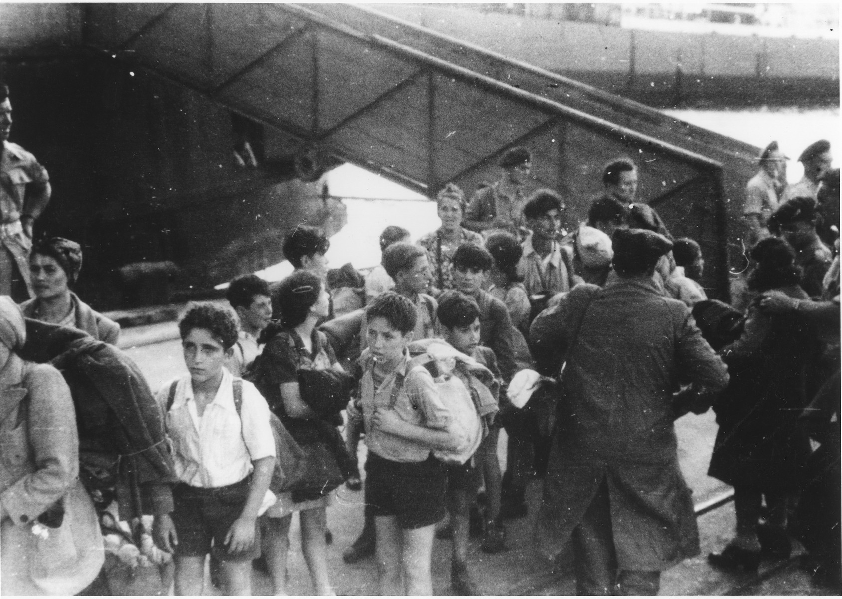 A group of children disembark from the illegal immigrant ship, Exodus 1947, onto the dock in Haifa harbor.