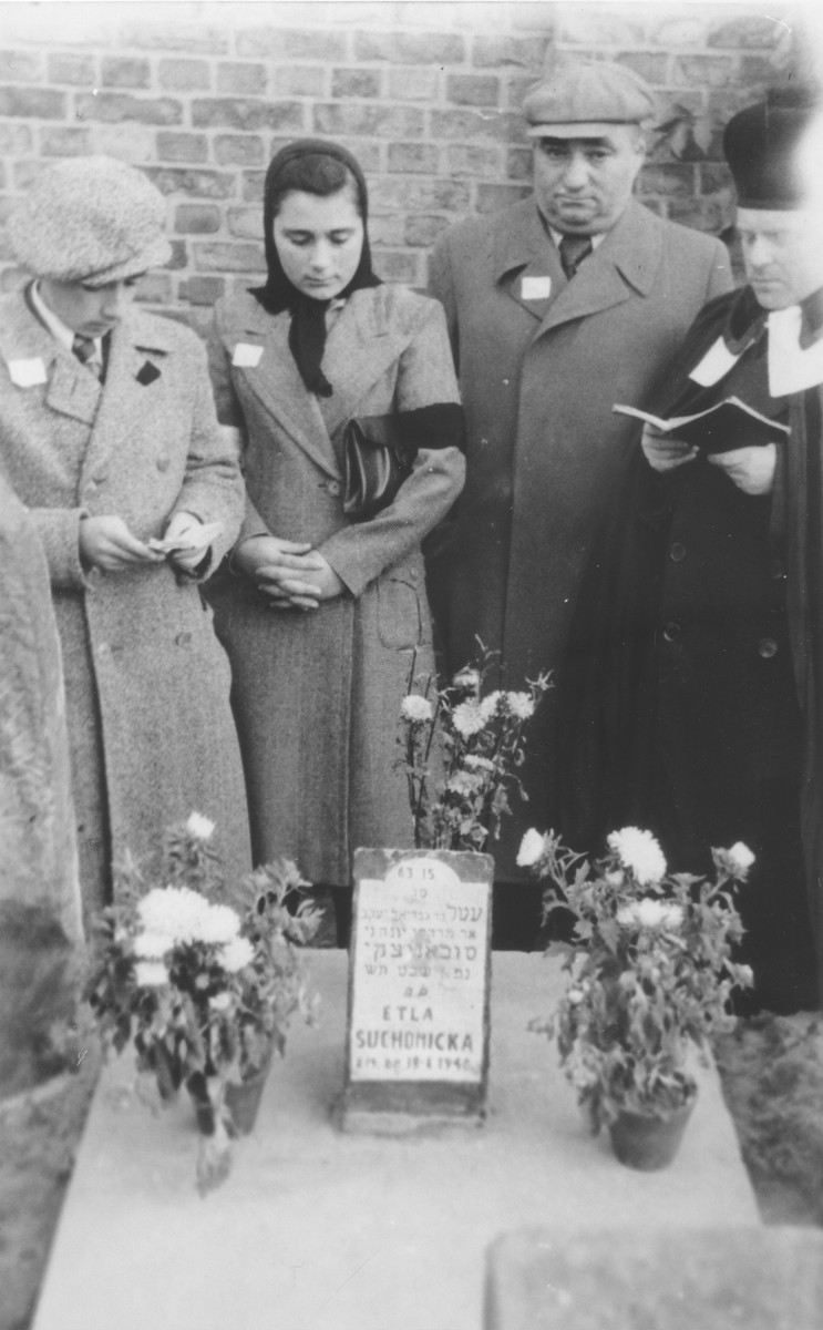 A rabbi or cantor leads the family of Etla Suchomicka in prayer at the unveiling of her tombstone at the Gesia cemetery in Warsaw.  Pictured from left to right are: Etla's son Leibl, her daughter Necha and her husband Mordcha.