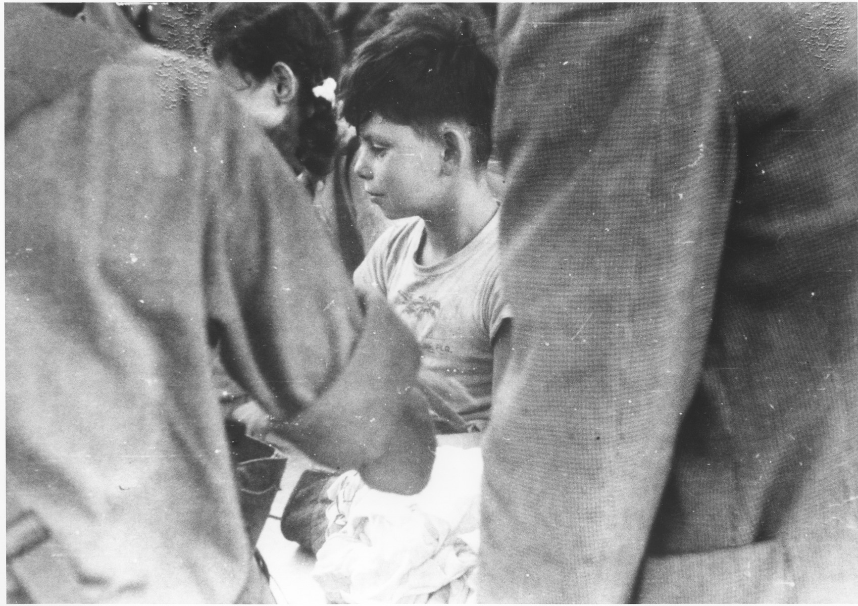 A young Jewish boy, who is one of the passengers on the illegal immigrant ship, Exodus 1947, has his papers checked by a British soldier on the dock in Haifa.