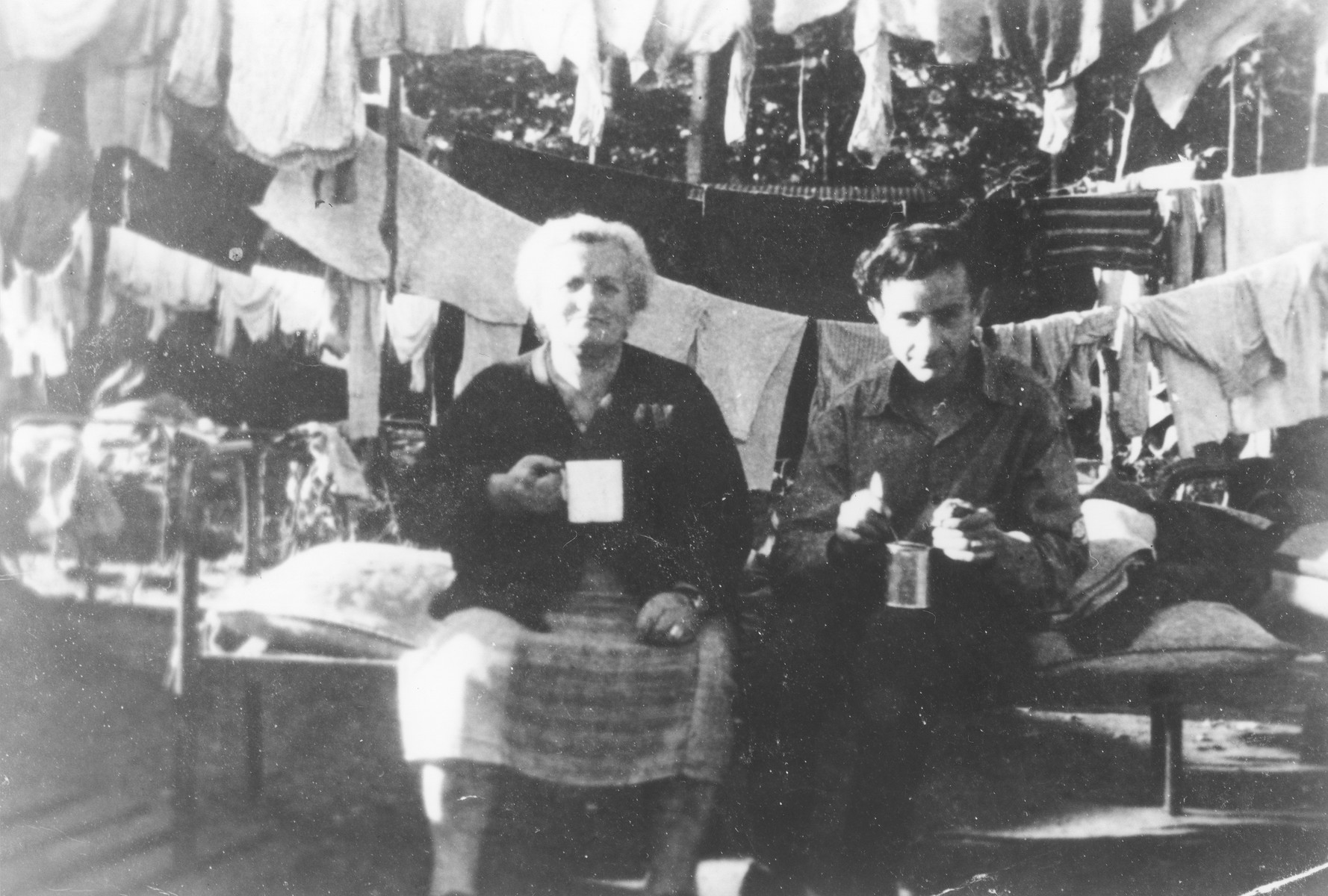 Two former passengers of the Exodus 1947 have a hot drink while sitting on a cot in the Poppendorf displaced persons camp.