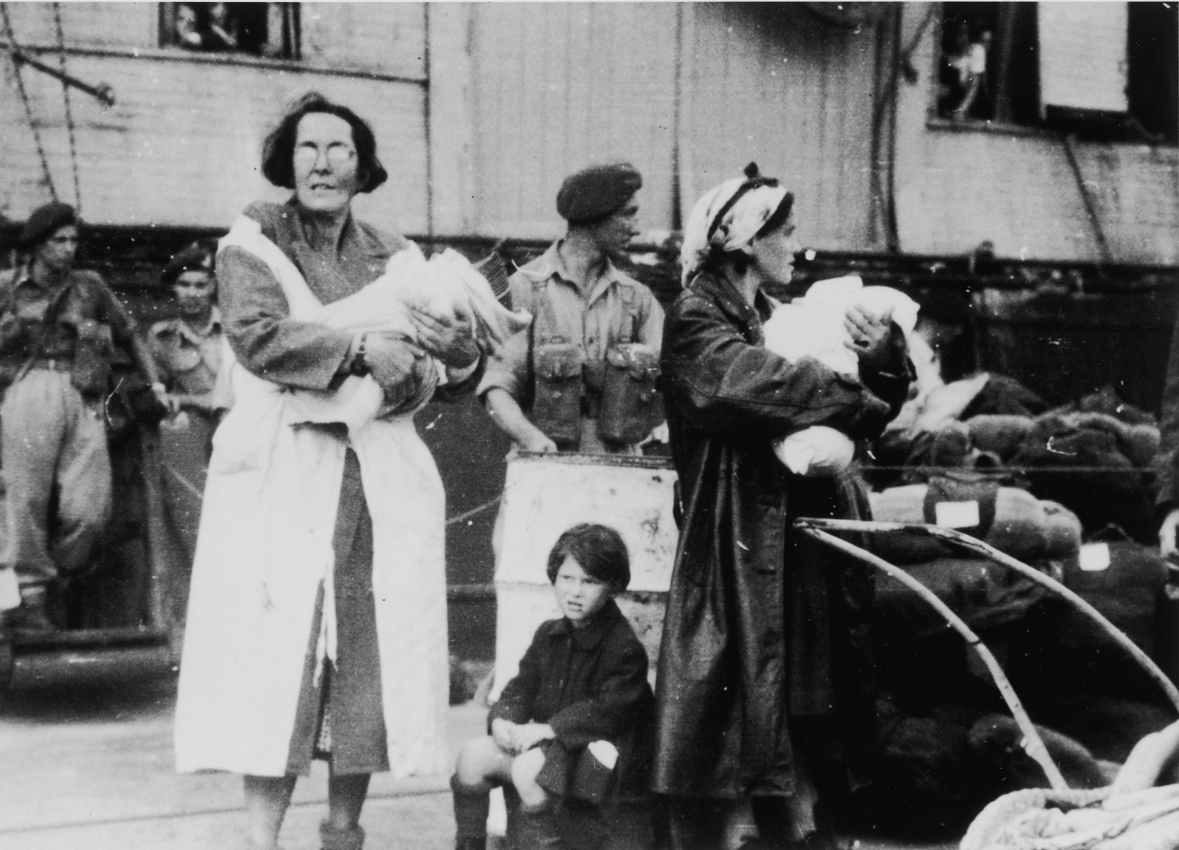 Two female passengers of the Exodus 1947 wait on the dock in Haifa holding infants who were born during the voyage.    The woman at the left is the grandmother of the infant she holds.  The child's mother died in childbirth.