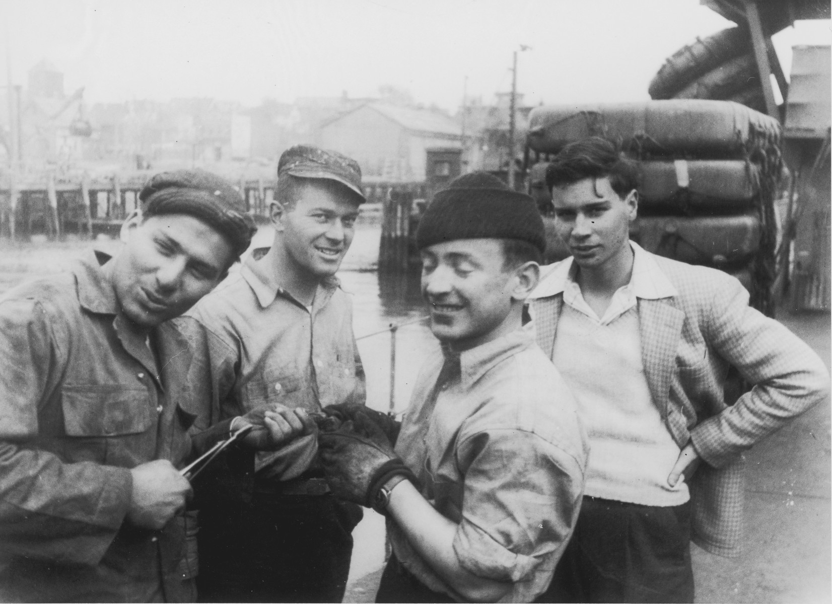 Four crew members of an illegal immigrant ship to Palestine [possibly the Haganah or the Josiah Wedgewood] pose at Brewer's Dry Dock, Staten Island on the day they set sail for Europe to pick up Jewish DPs.  Pictured from left to right are: the unidentified bosin, David Fendel, Hyman Schechtman and Nadav Halevy.