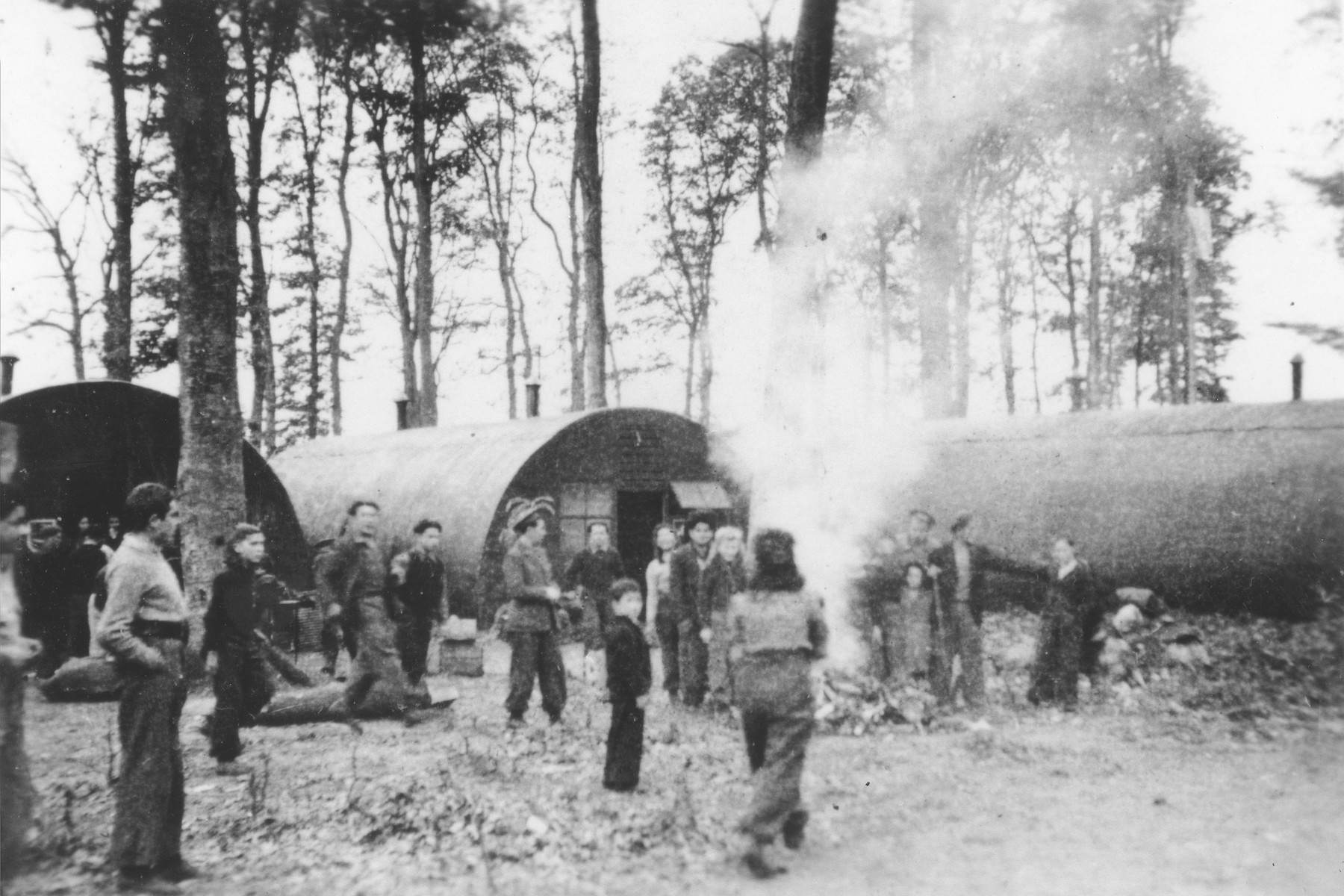 Former passengers on the Exodus 1947 gather around a campfire outside a row of Nissen huts in the Poppendorf displaced persons camp.