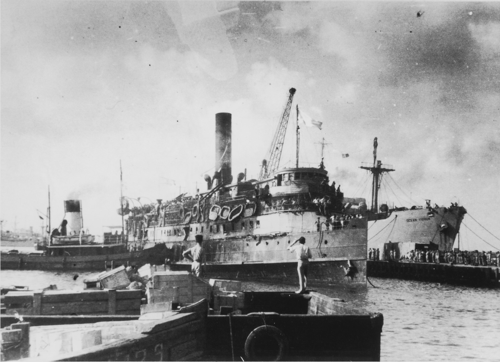"View of the battered illegal immigrant ship, Exodus 1947, docked in the port of Haifa alongside the British ""comfort ship,"" Ocean Vigour, to which the Exodus passengers are being transferred."