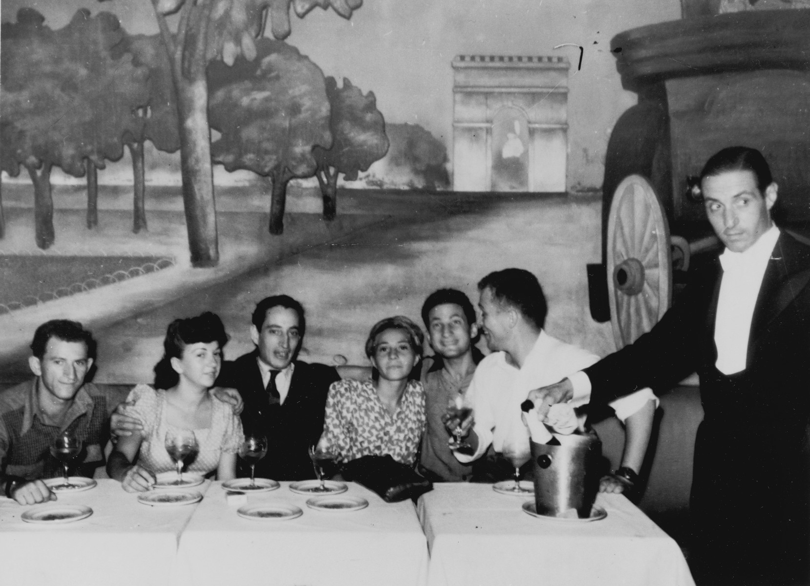 Crew members of the illegal immigrant ship Exodus 1947 drink a toast in a restaurant while on shore leave in Marseilles shortly before sailing for Palestine.  Among those pictured are: Renee and Bernard Marks (fourth and fifth from the left), Avraham Siegel (far left) and Bentley Forman (sixth from the left).