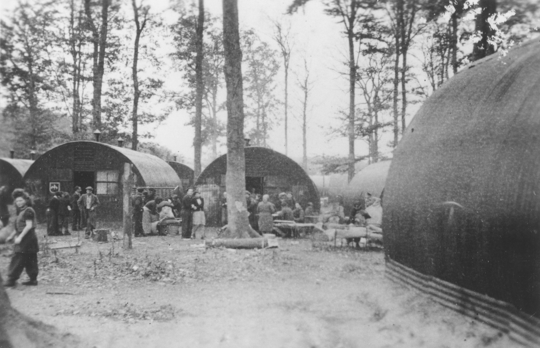Former passengers on the Exodus 1947 gather outside a row of Nissen huts in the Poppendorf displaced persons camp.