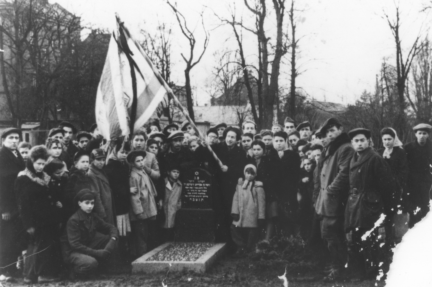 Former passengers on the Exodus 1947 gather around the grave of a comrade who died [probably in the Jewish cemetery of Luebeck].