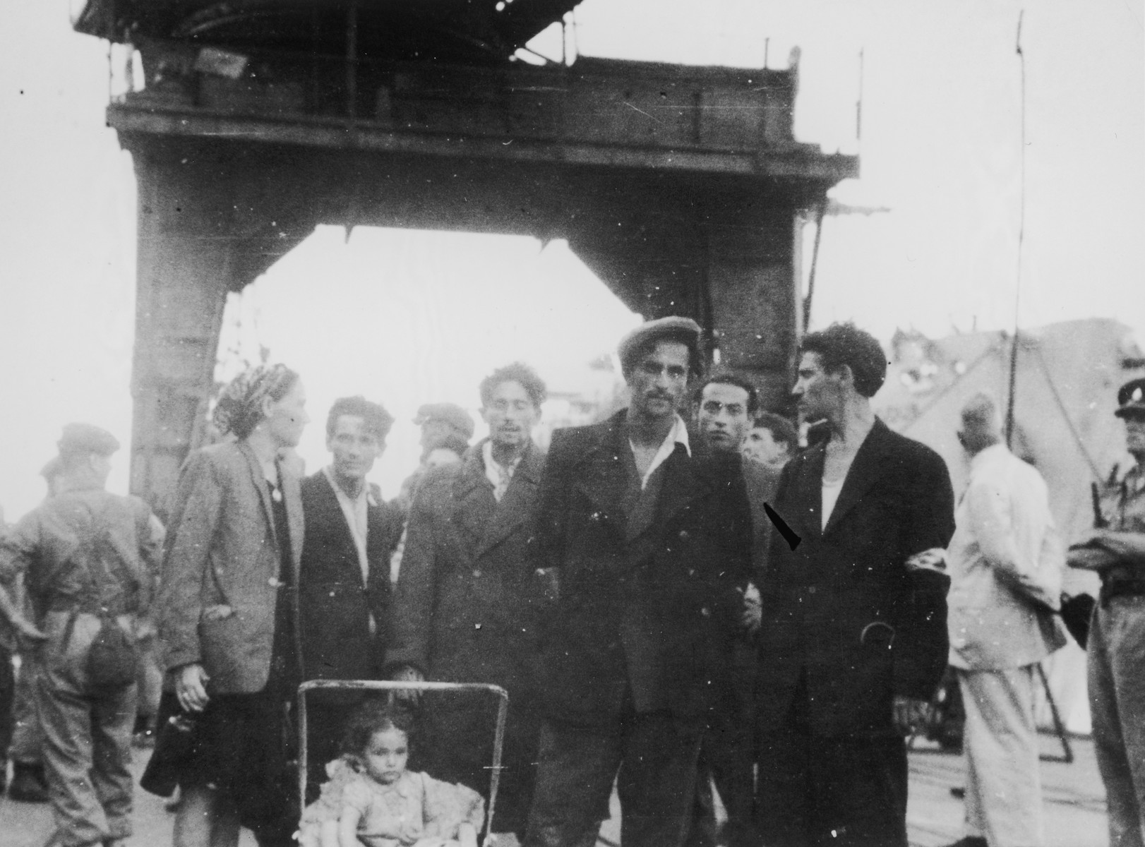 Passengers from the illegal immigrant ship, Exodus 1947, wait on the pier in Haifa harbor to be transferred to British ships.    Pictured at the right (in the white suit) is a United Nations official who was present to observe the transfer process.