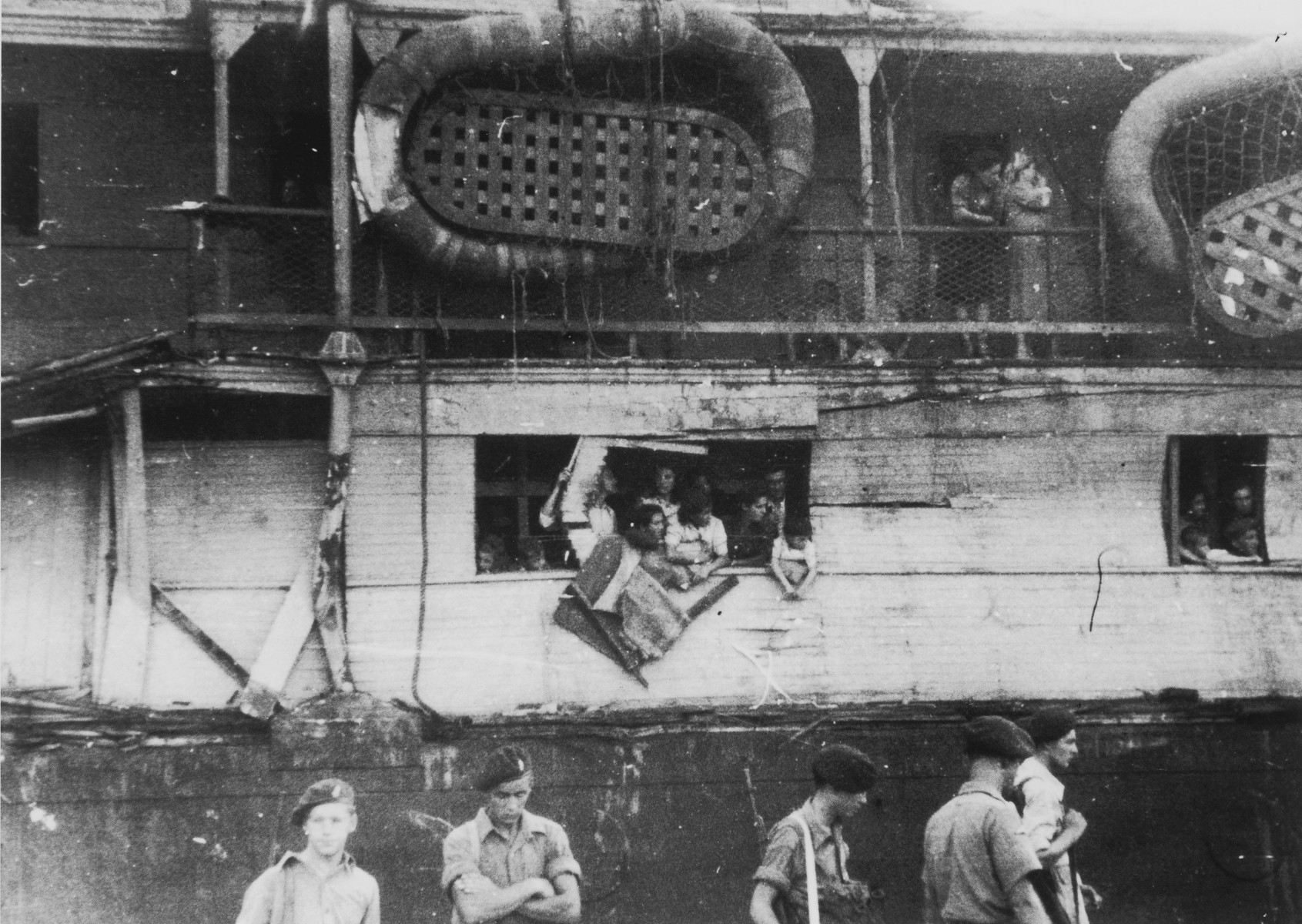 Jewish DPs on the battered illegal immigrant ship, Exodus 1947, look out onto the dock lined with British soldiers in the port of Haifa.