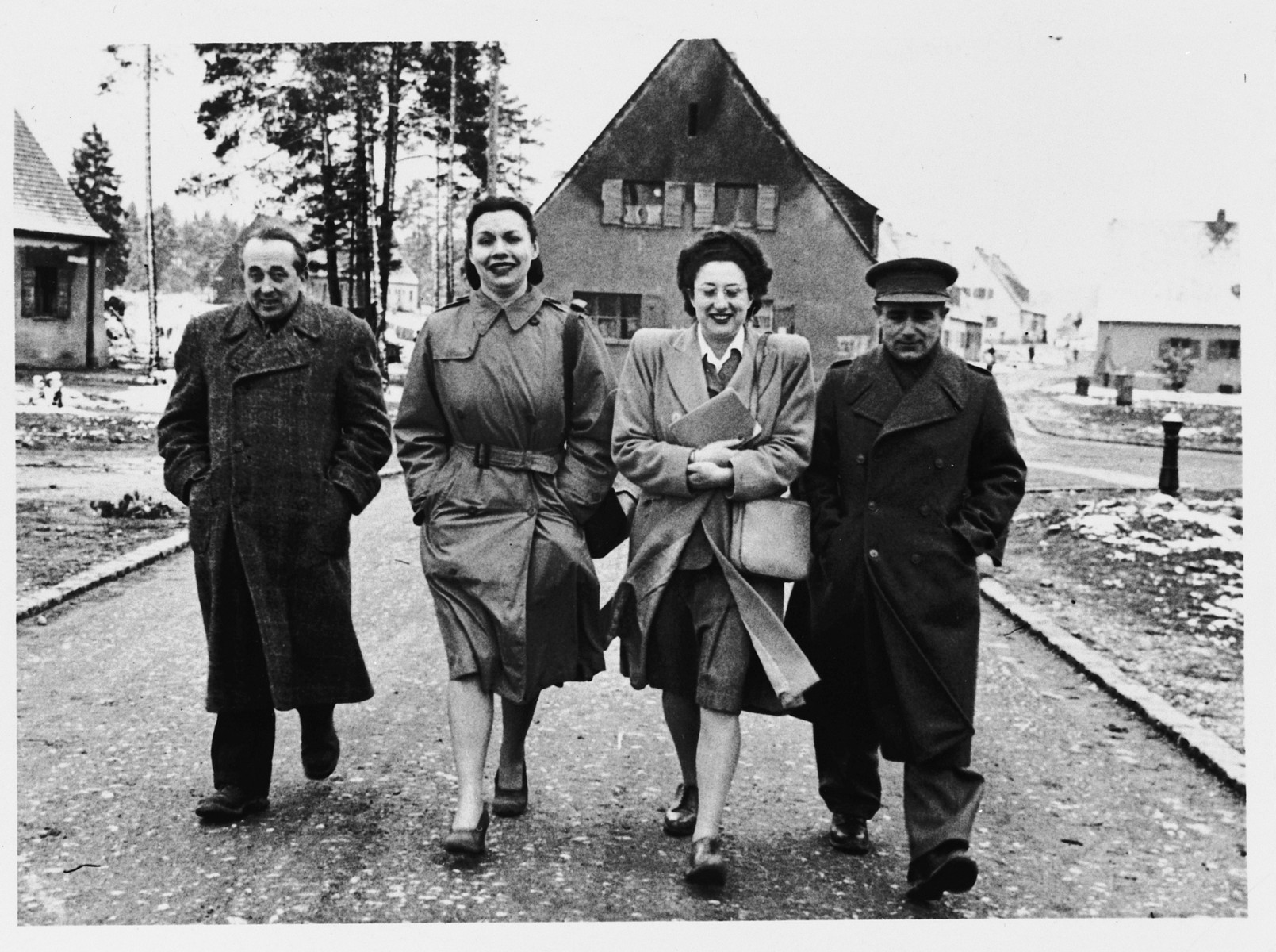 Two men and two women walk down a snow-dusted lane in the Foehrenwald DP camp.