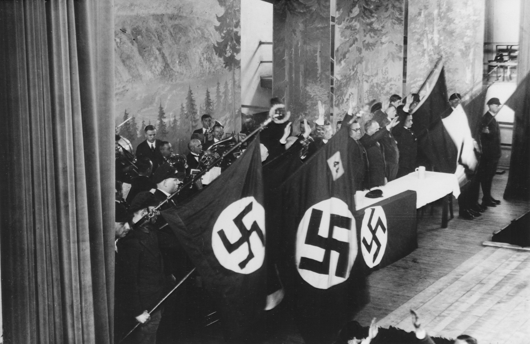 Nazi party officials give the Hitler salute at a gathering in the Stadthalle in Bad Blankenburg.  An orchestra performs behind the speakers' table.