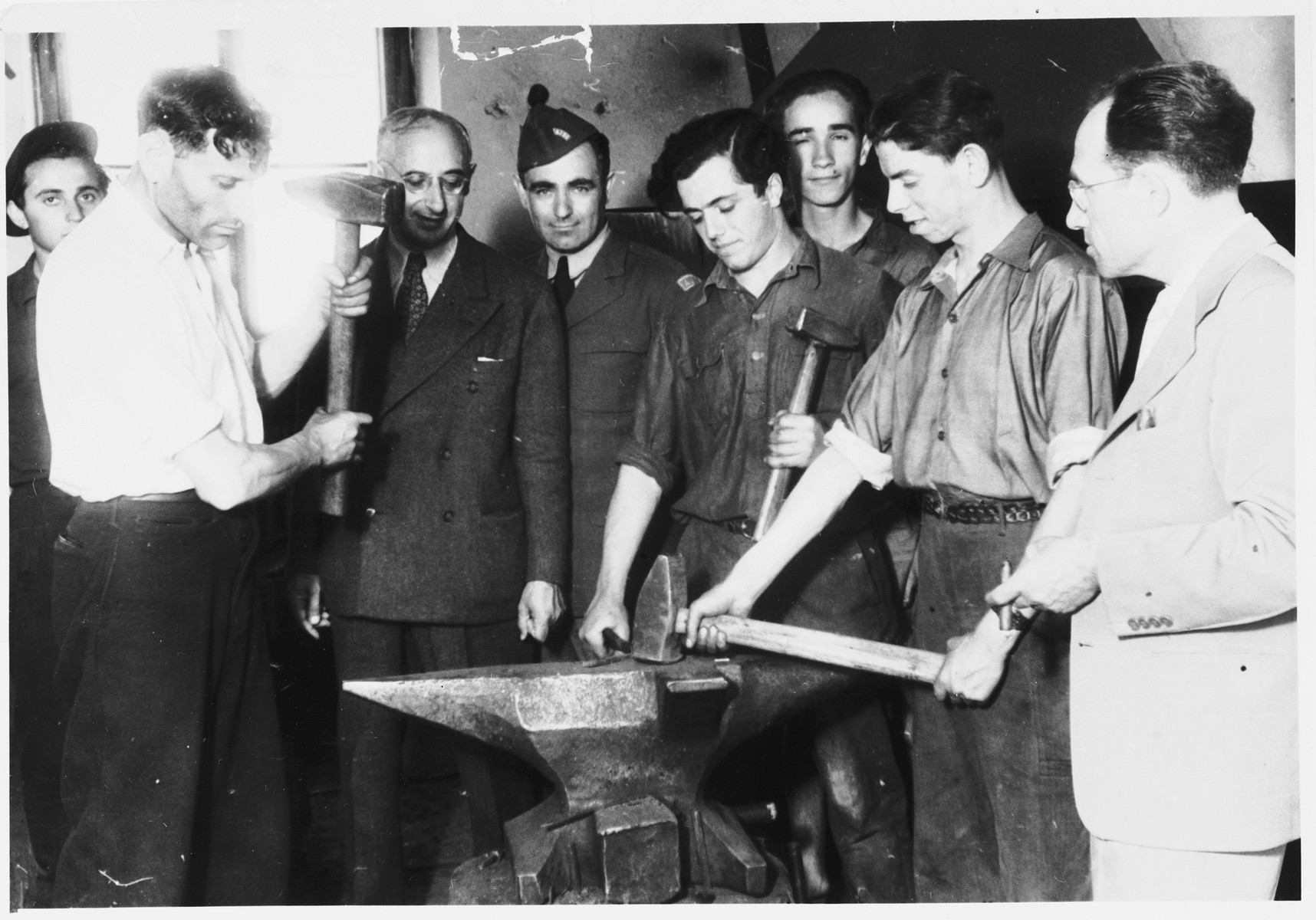 Issak Libstug, wearing his AJDC uniform, watches men demonstrate the use of an anvil in a workshop in the Foehrenwald displaced persons camp.