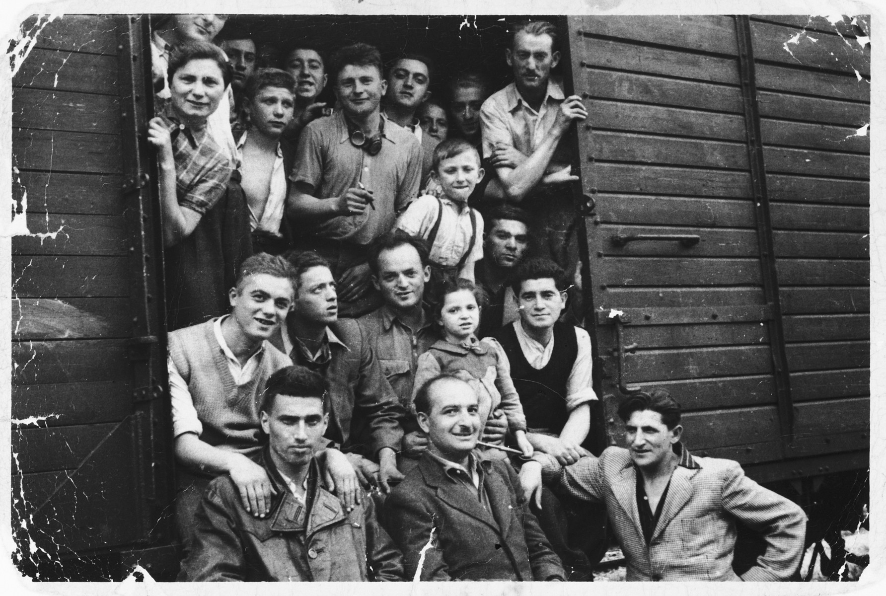 Jewish DPs look out the door of a cattle car as they cross the border from Austria into Italy.  Those pictured include Baruch and Zev Winer .  The boy above them is Moti Ravid.  Also pcitured are Abraham, Rachel and Channa Lisogurski.