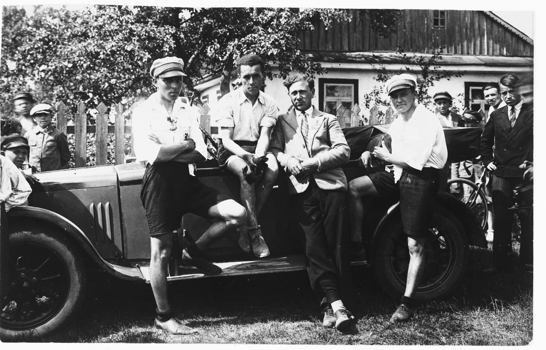 Shmuel Gertner and his friends gather around a shiny automobile.